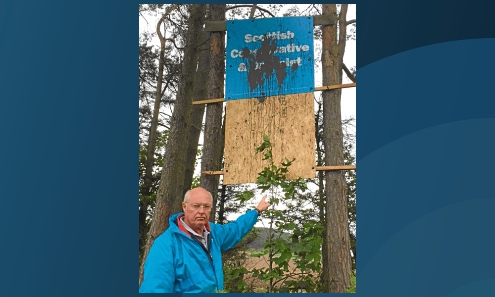 Tony Miklinski, Conservative candidate for North East Fife, with one of the defaced banners.