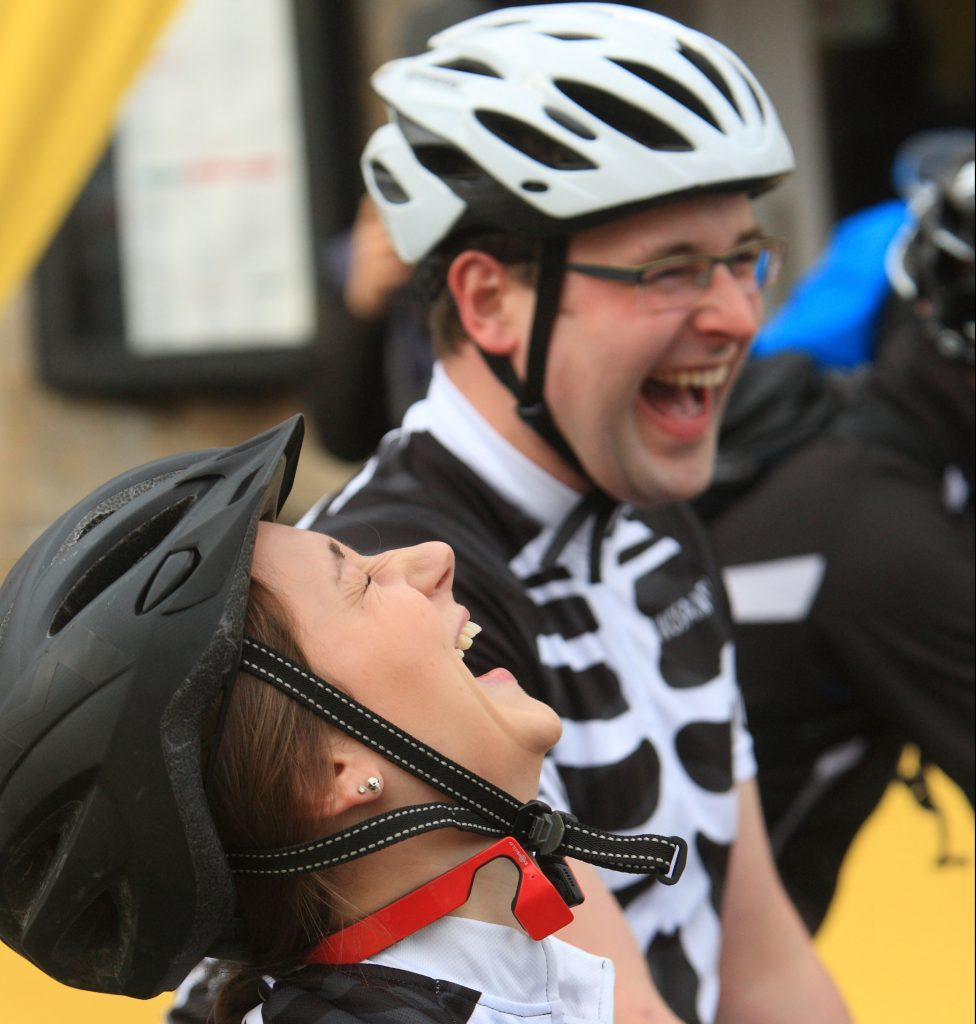 Cyclists share a joke at the start.