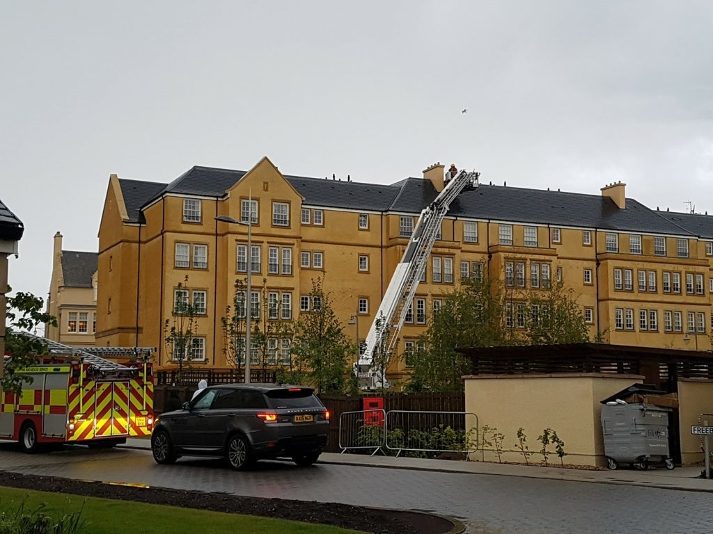 Firefighters check the roof of the flats at Abbey Park View in St Andrews after it was struck by lightning