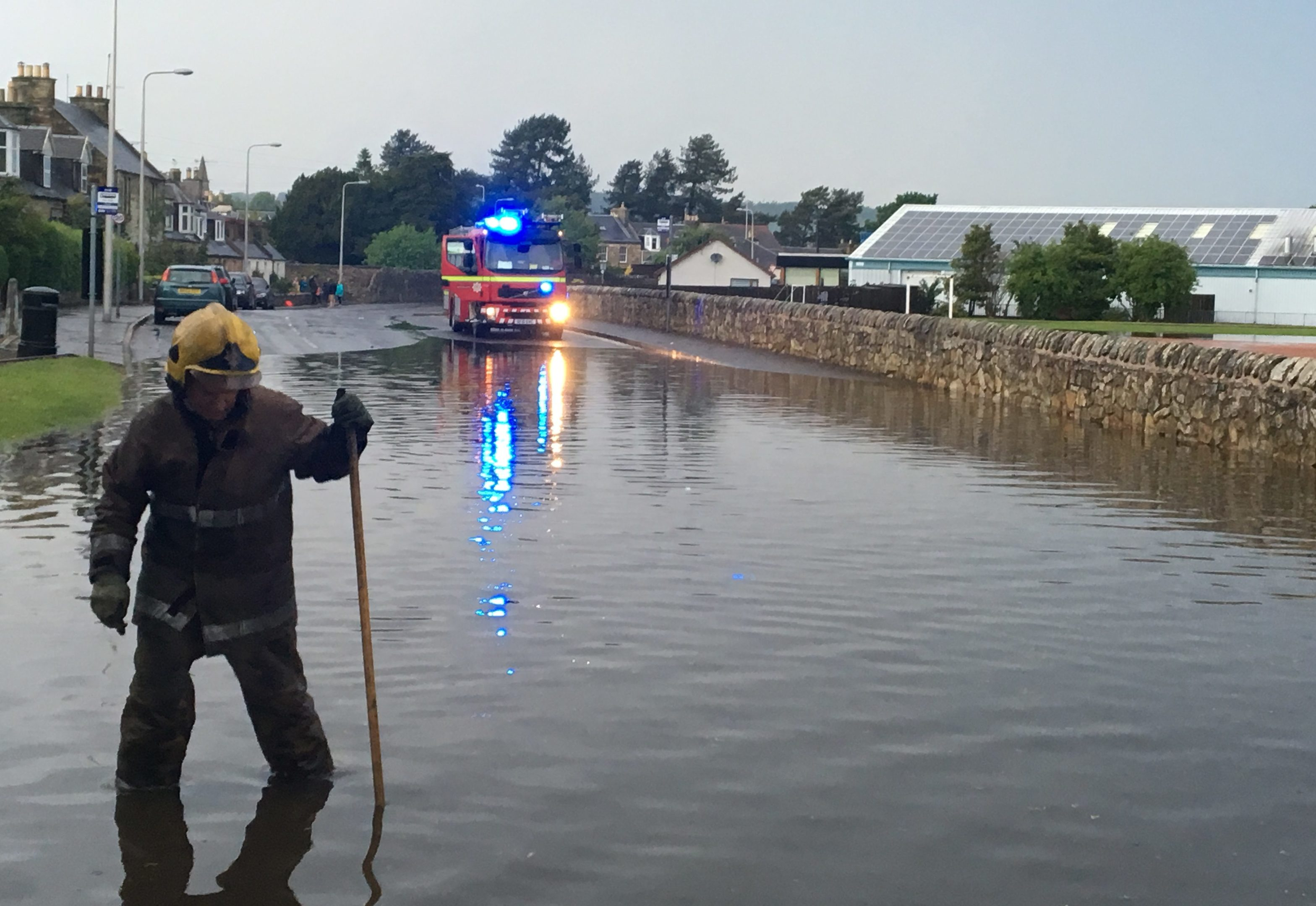 Firefighters work hard to unblock drains after flash floods in Ceres Road, Cupar, on Saturday,