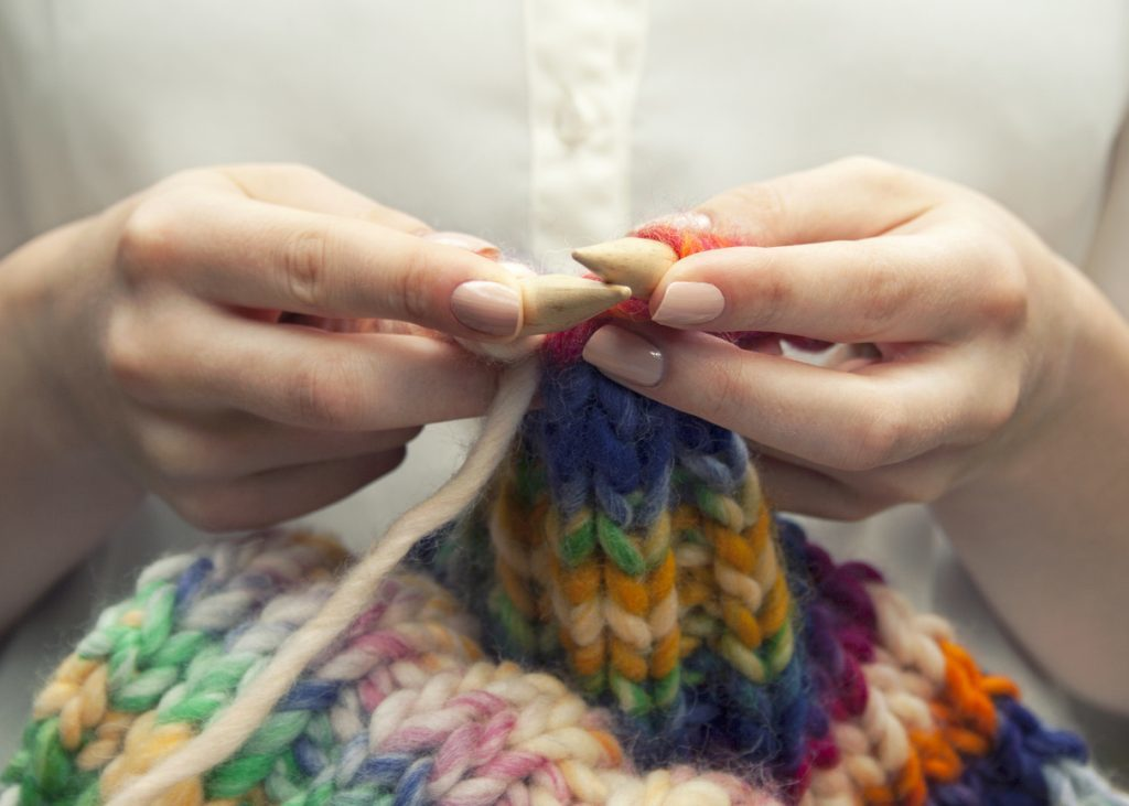 Young woman knitting a woolen colorful scarf, closeup