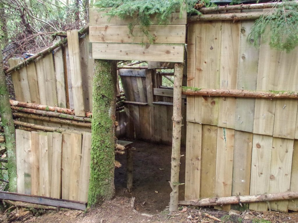 The exterior of the sizeable woodland hut created within the woods.
