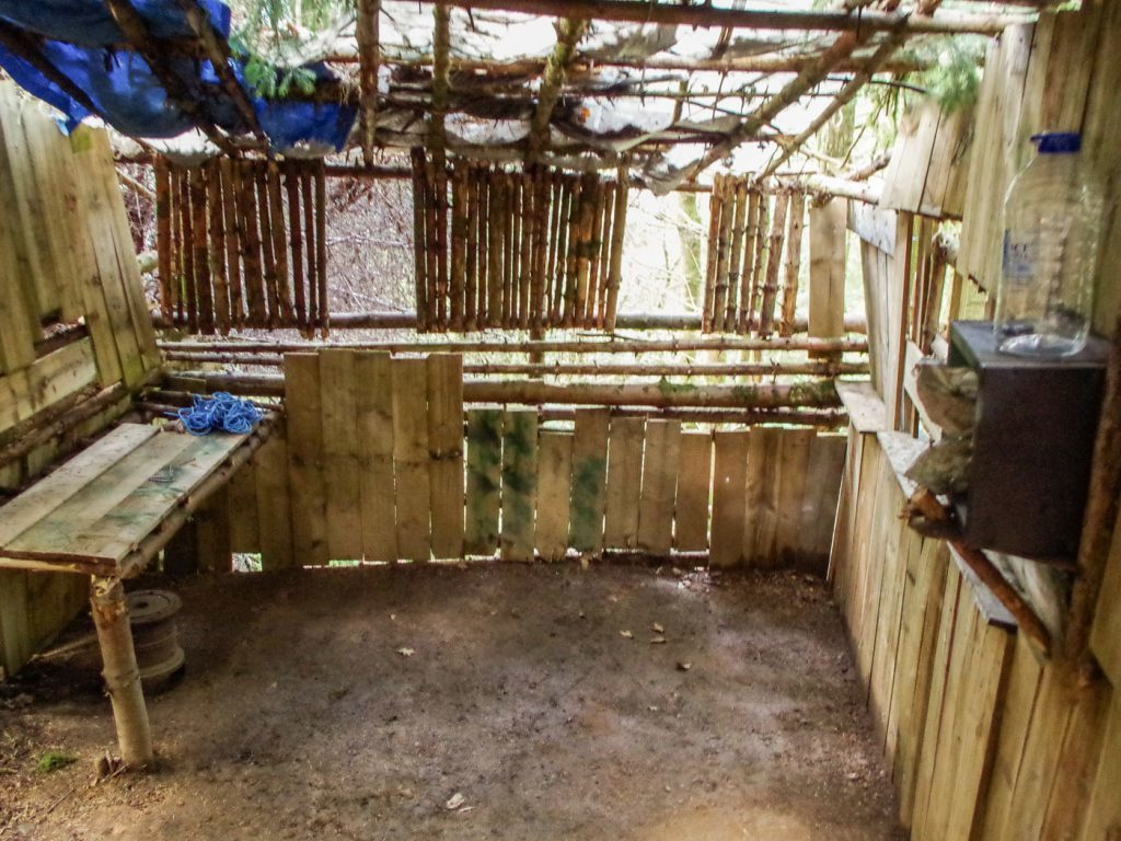 The interior of the substantial hut illegally erected in the woods. Two flags, the stars and stripes and a Union Jack, adorn the opposite wall.