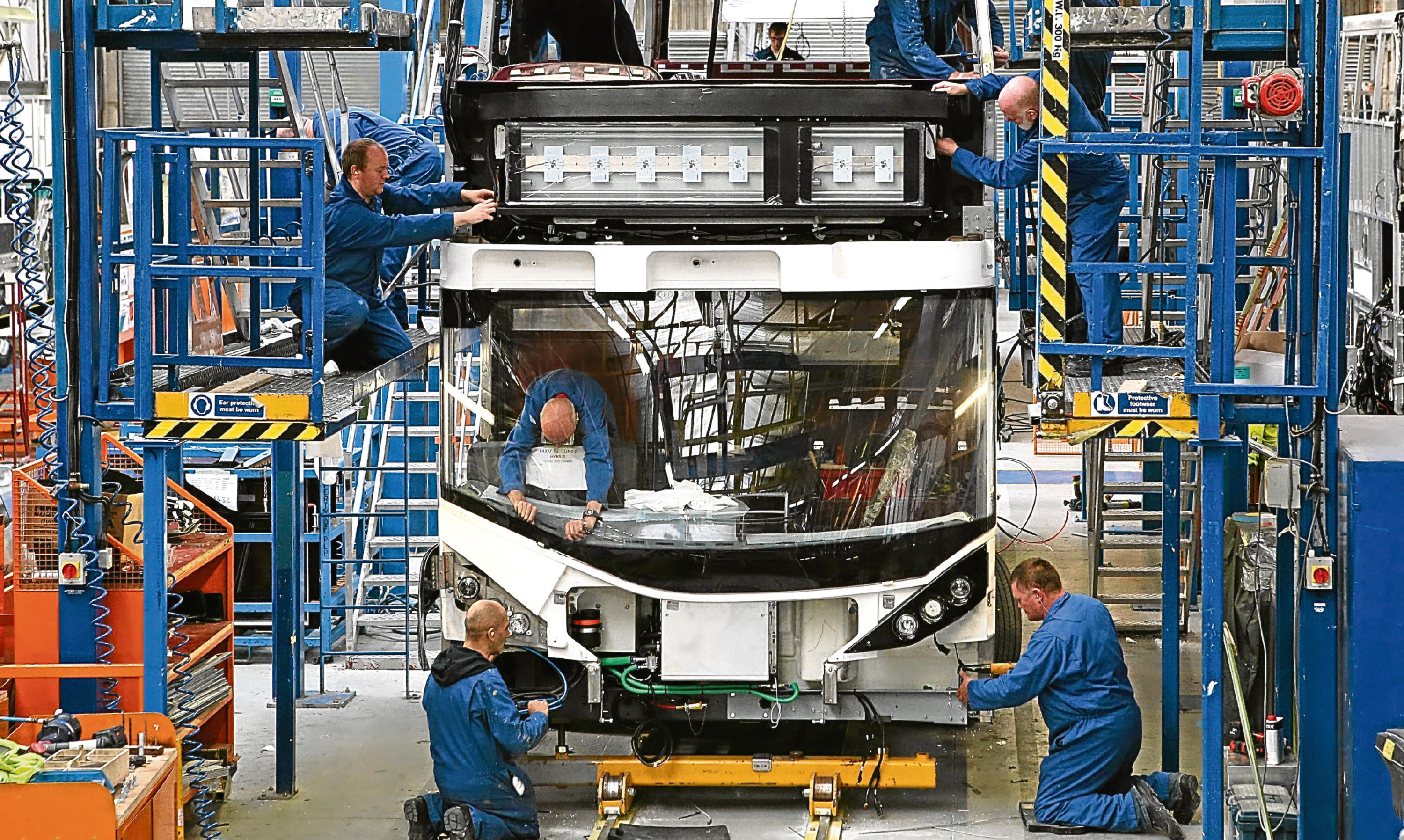 Alexander Dennis technicians work on a new bus build.