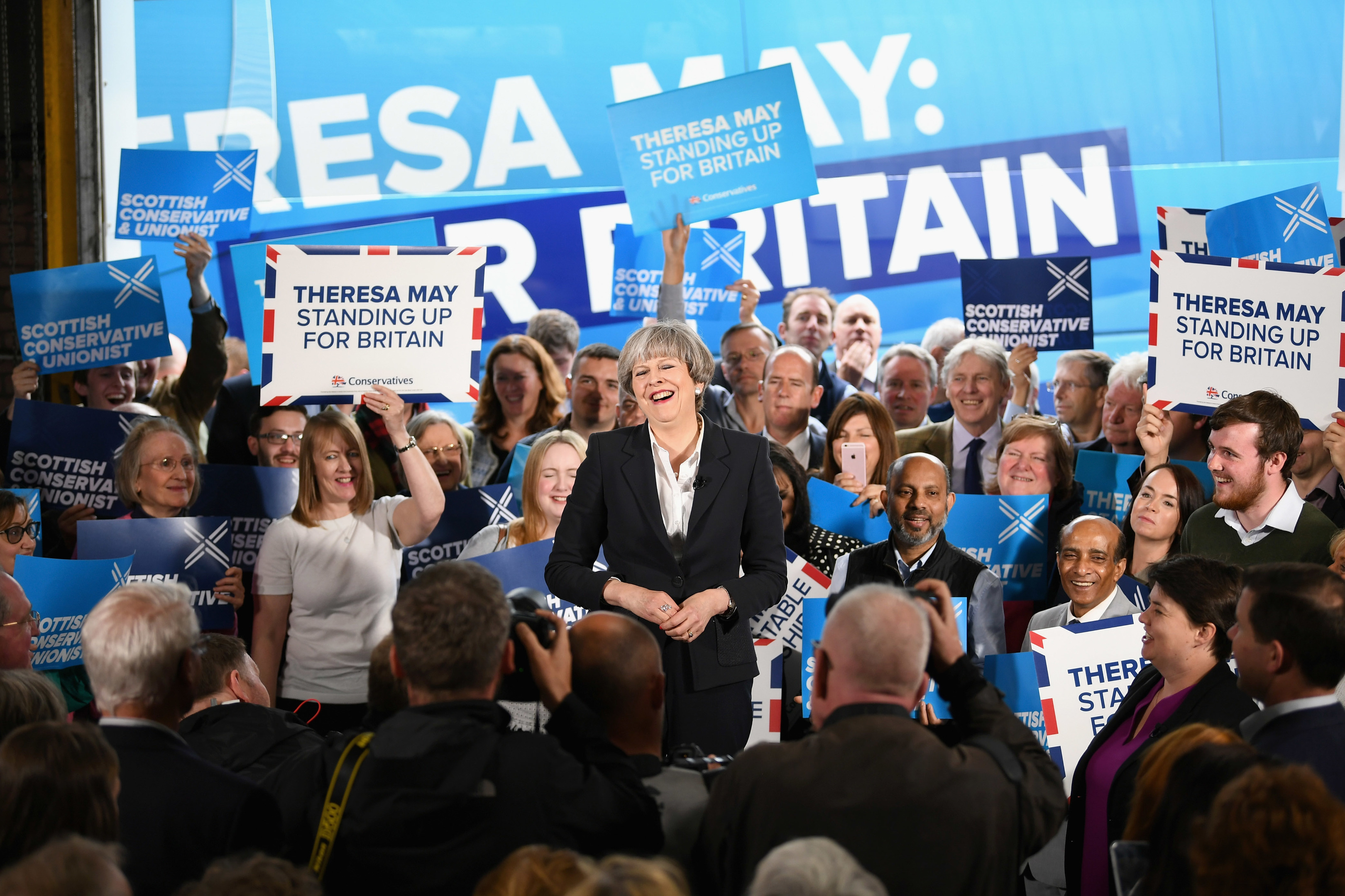 Prime Minister Theresa May laughs as she delivers a speech at Clockwork Removals in Edinburgh.