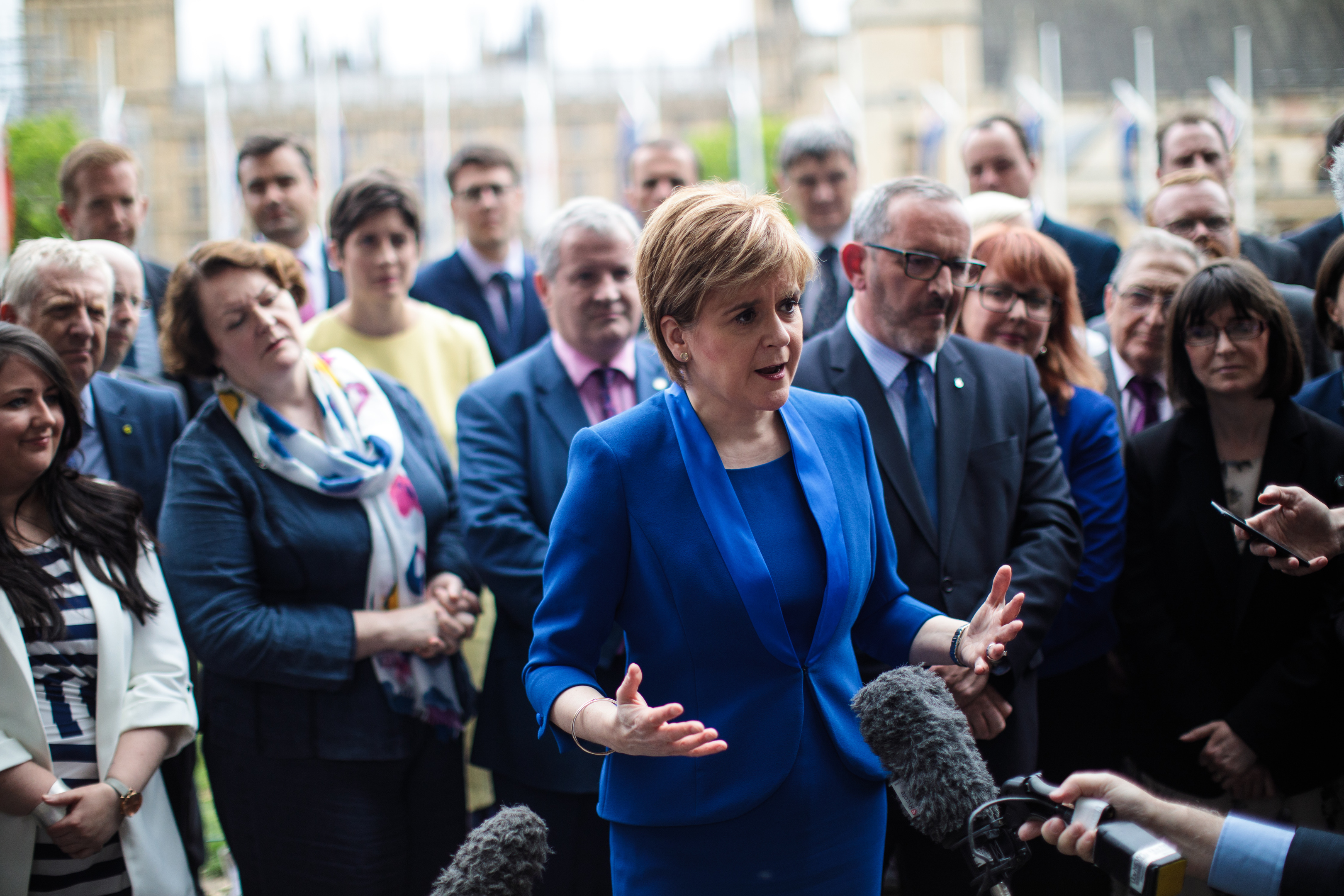 SNP leader Nicola Sturgeon speaks to the media as she stands in front of SNP MPs elected in the general election during a photocall in Parliament Square.