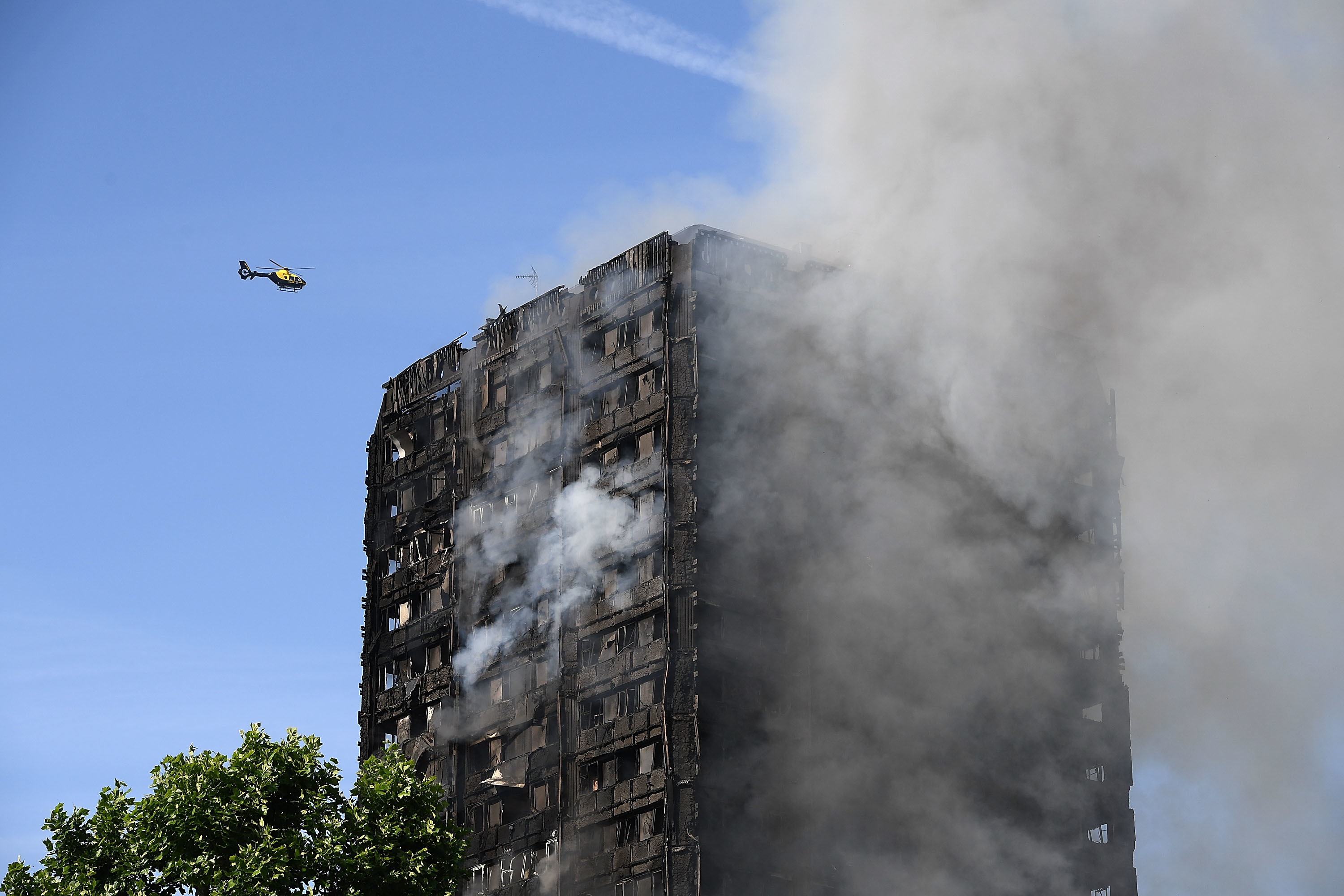 A heicopter circles as smoke rises from the building after a huge fire engulfed the 24 story Grenfell Tower