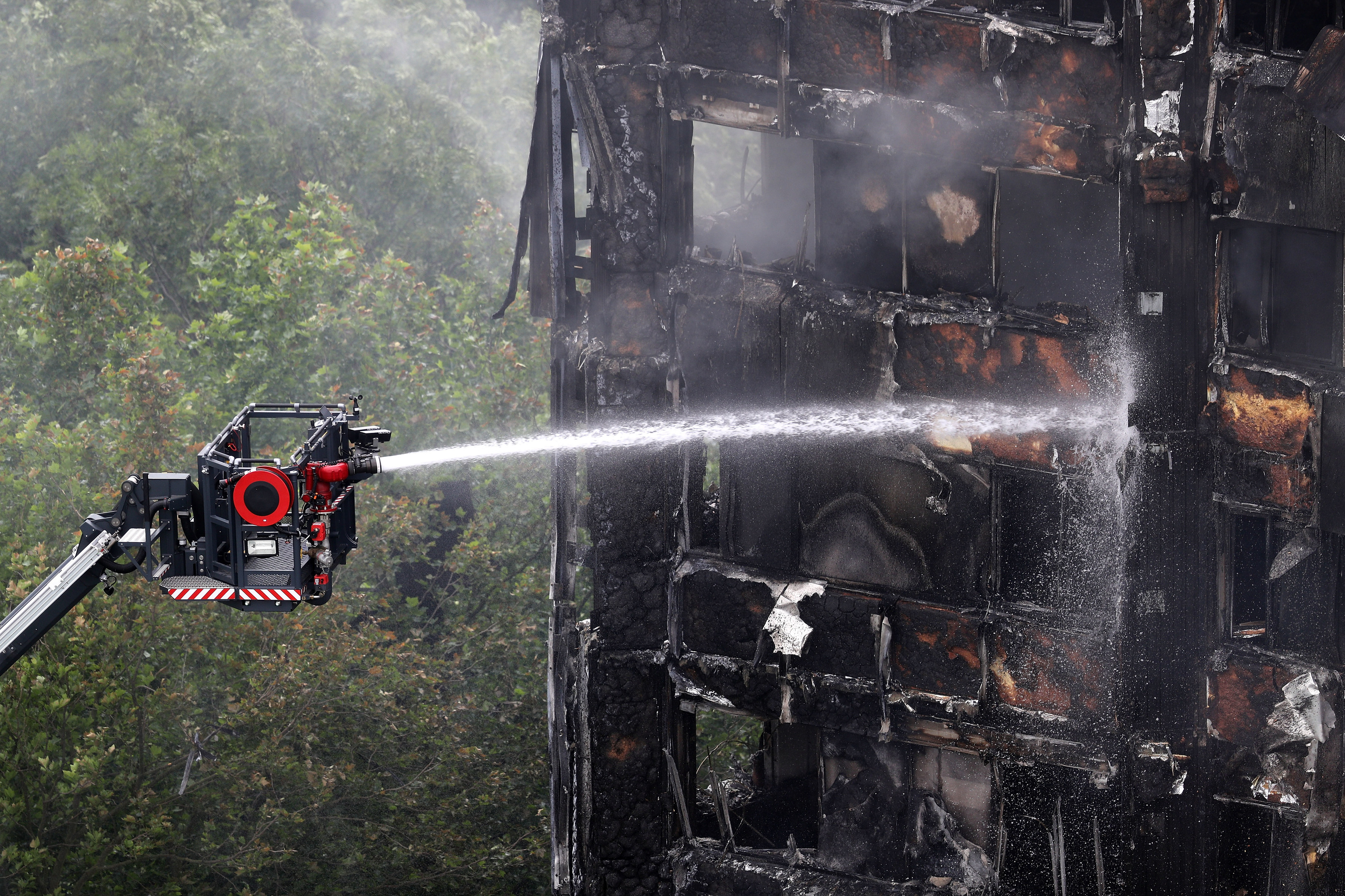 A firefighter continues to douse the fire at Grenfell Tower on June 15.
