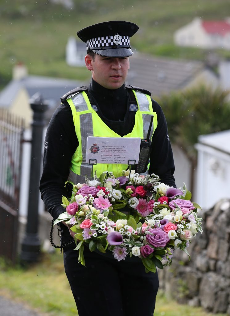 Flowers are laid by an officer from Police Scotland on behalf of the Chief Constable of Greater Manchester Police and the Mayor of Greater Manchester outside the Church of Our Lady, Star of the Sea, in Castlebay.