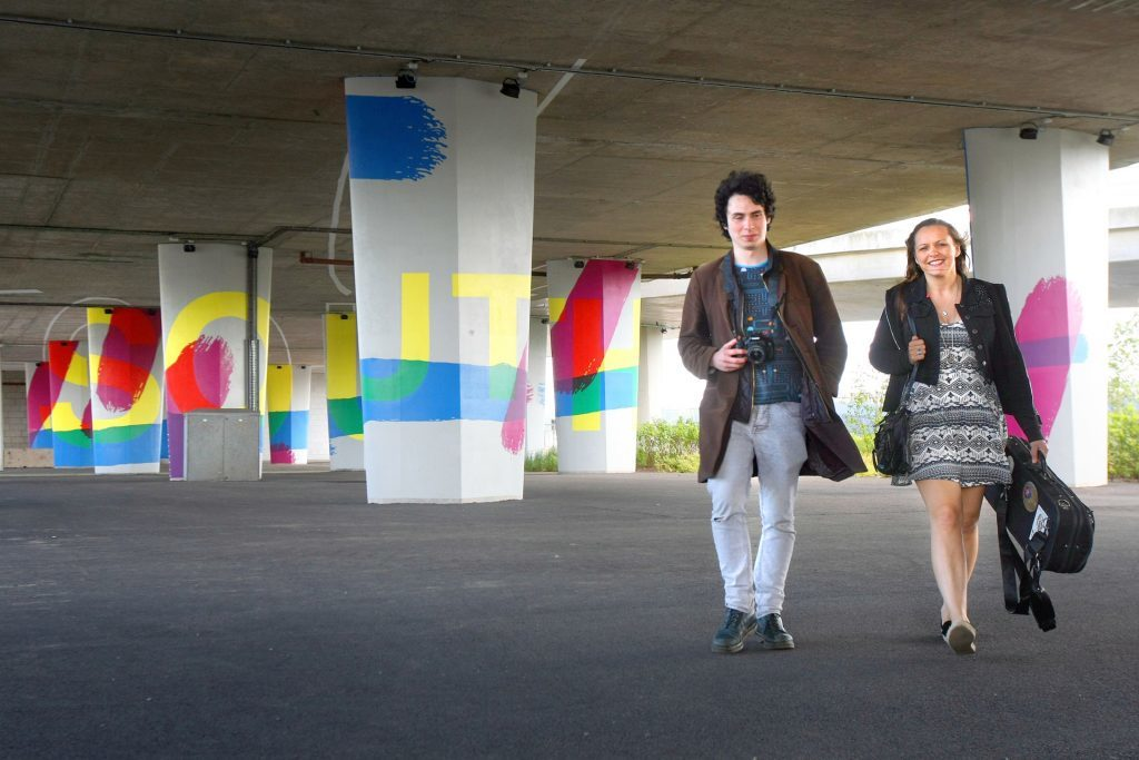 Tay Road Bridge columns with passers-by Julian Joseph and Laura McGhee.