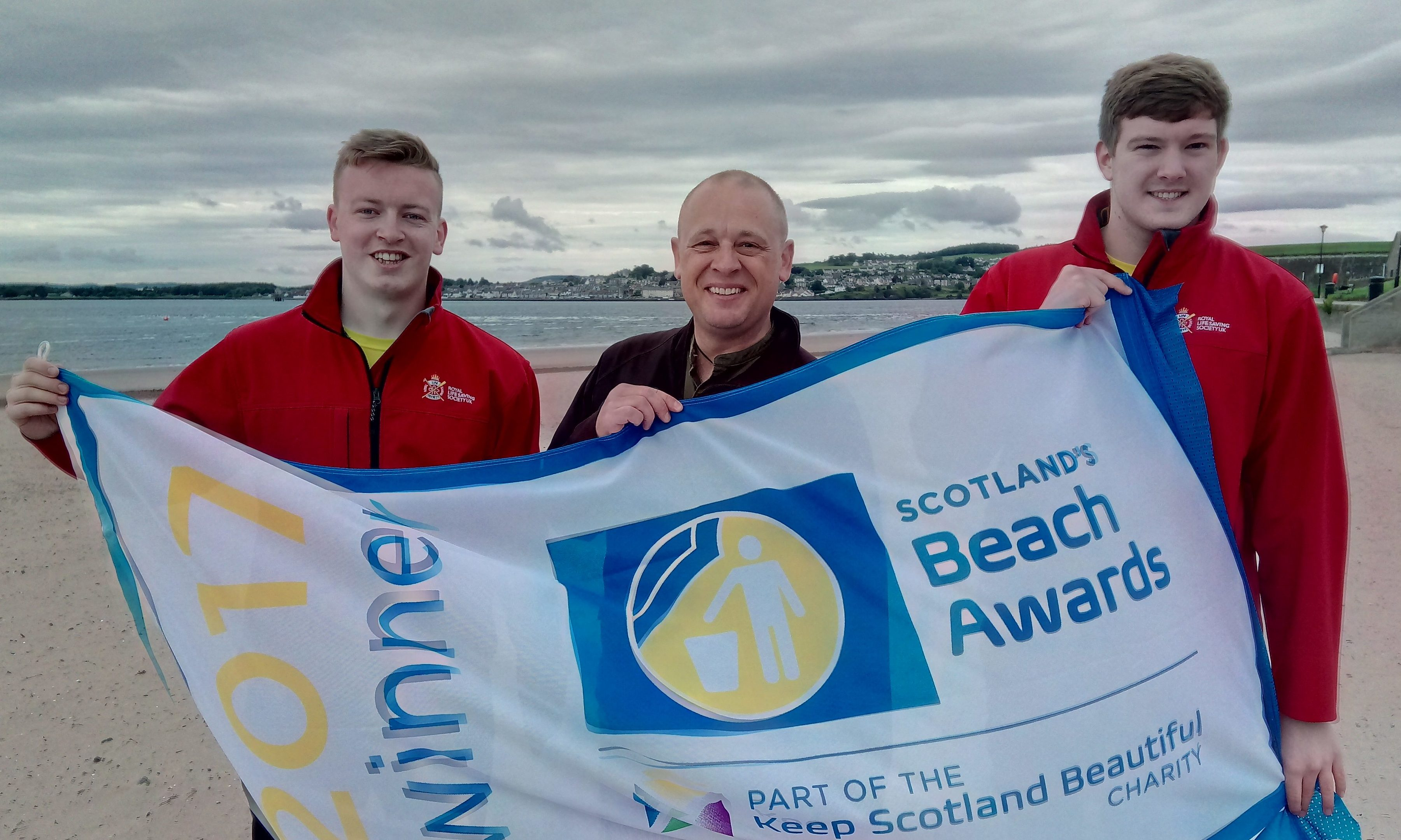 Lifeguards Kyle Doull and Sam Muir celebrate with Councillor Cordell.