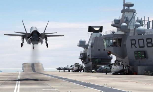A F-35B Lightning II jet landing vertically on the Royal Navy's new aircraft carrier HMS Queen Elizabeth.