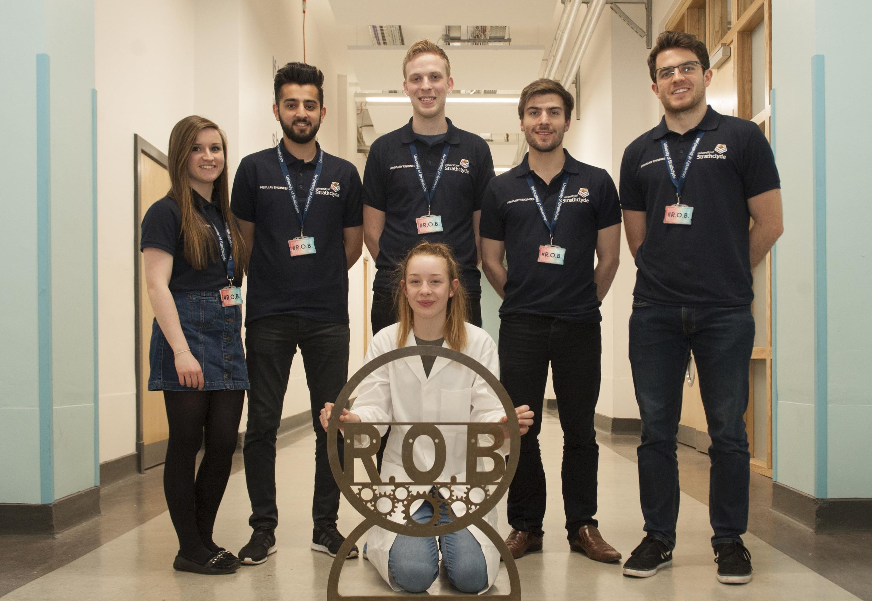 Grace Finlay, Primary Engineer invention winner, with part of her Roll Over Bench invention, and University of Strathclyde's Engineering students, who are helping to build it