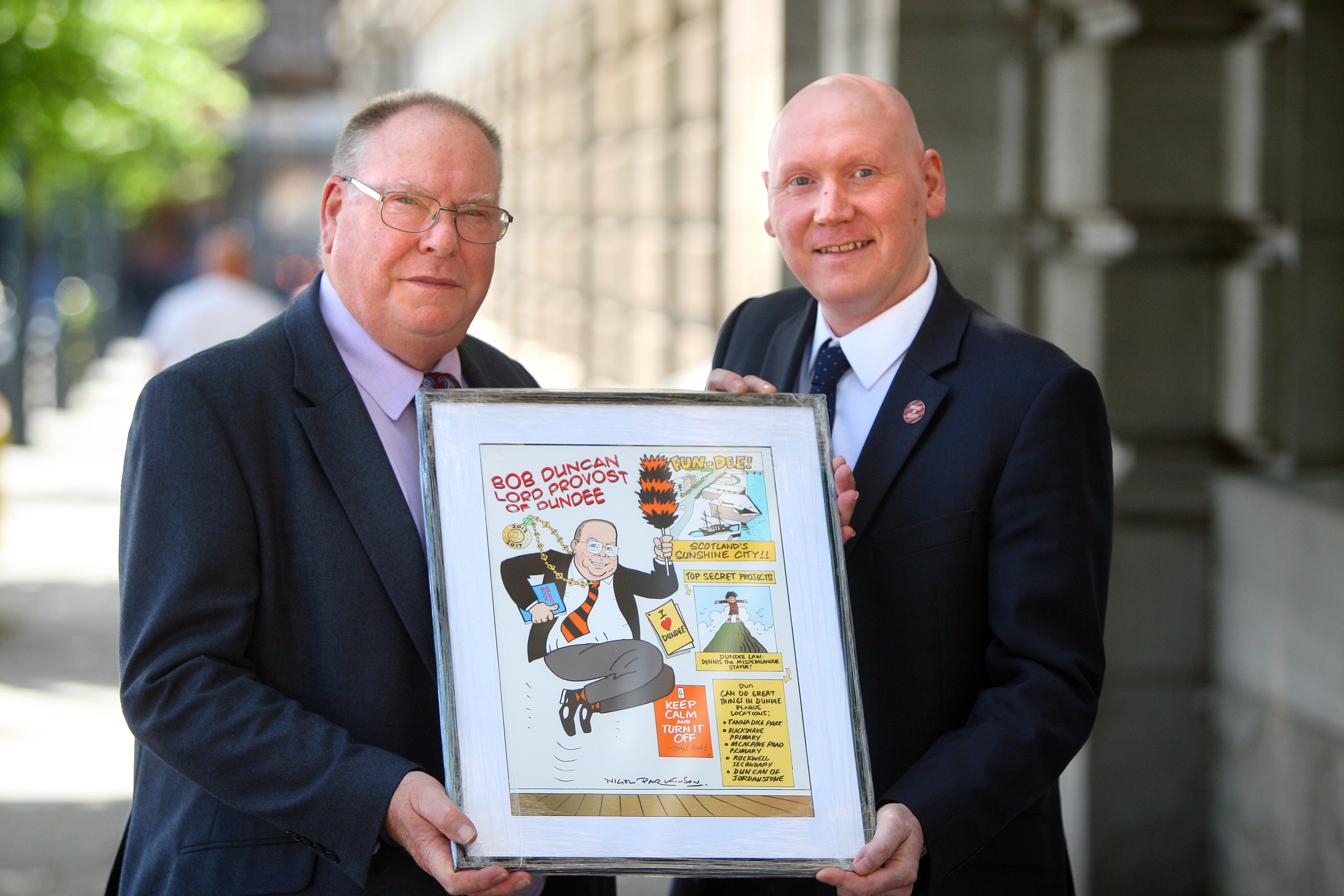 Bob Duncan being presented with a Beano style caricature by Craig Graham, managing editor at Beano Studios.