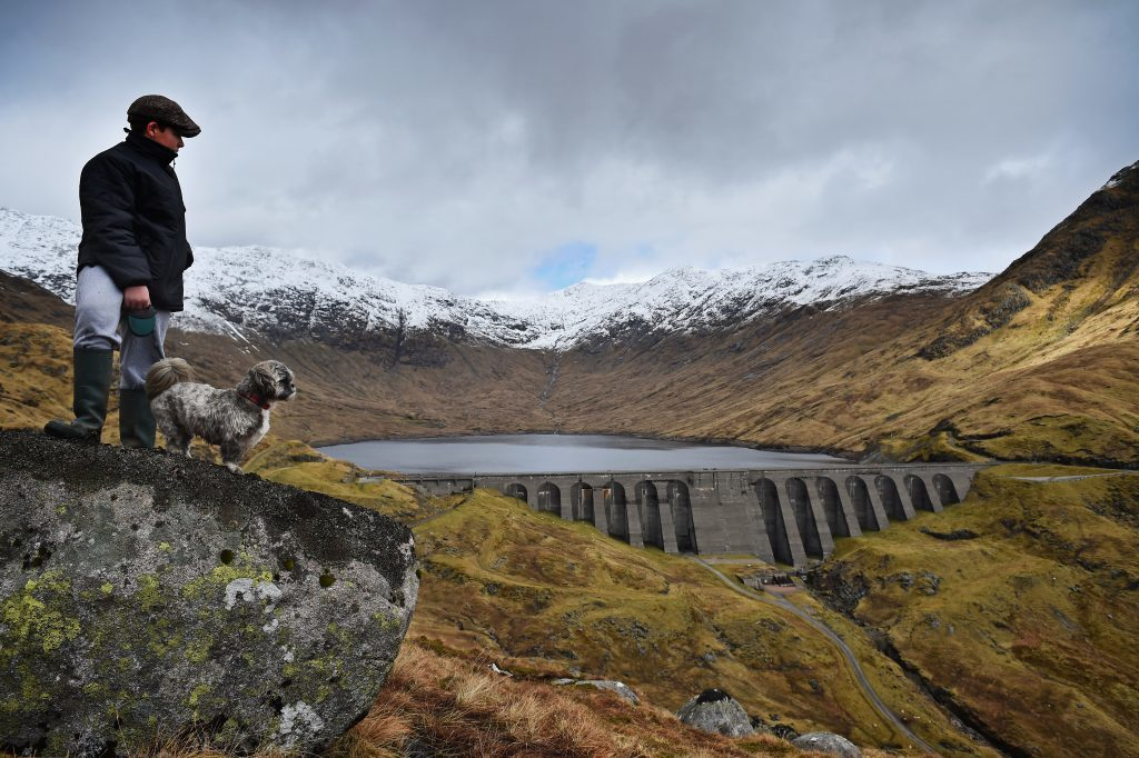 A boy and his dog view Cruachan hydro electric power station in Argyll on March 30, 2016.