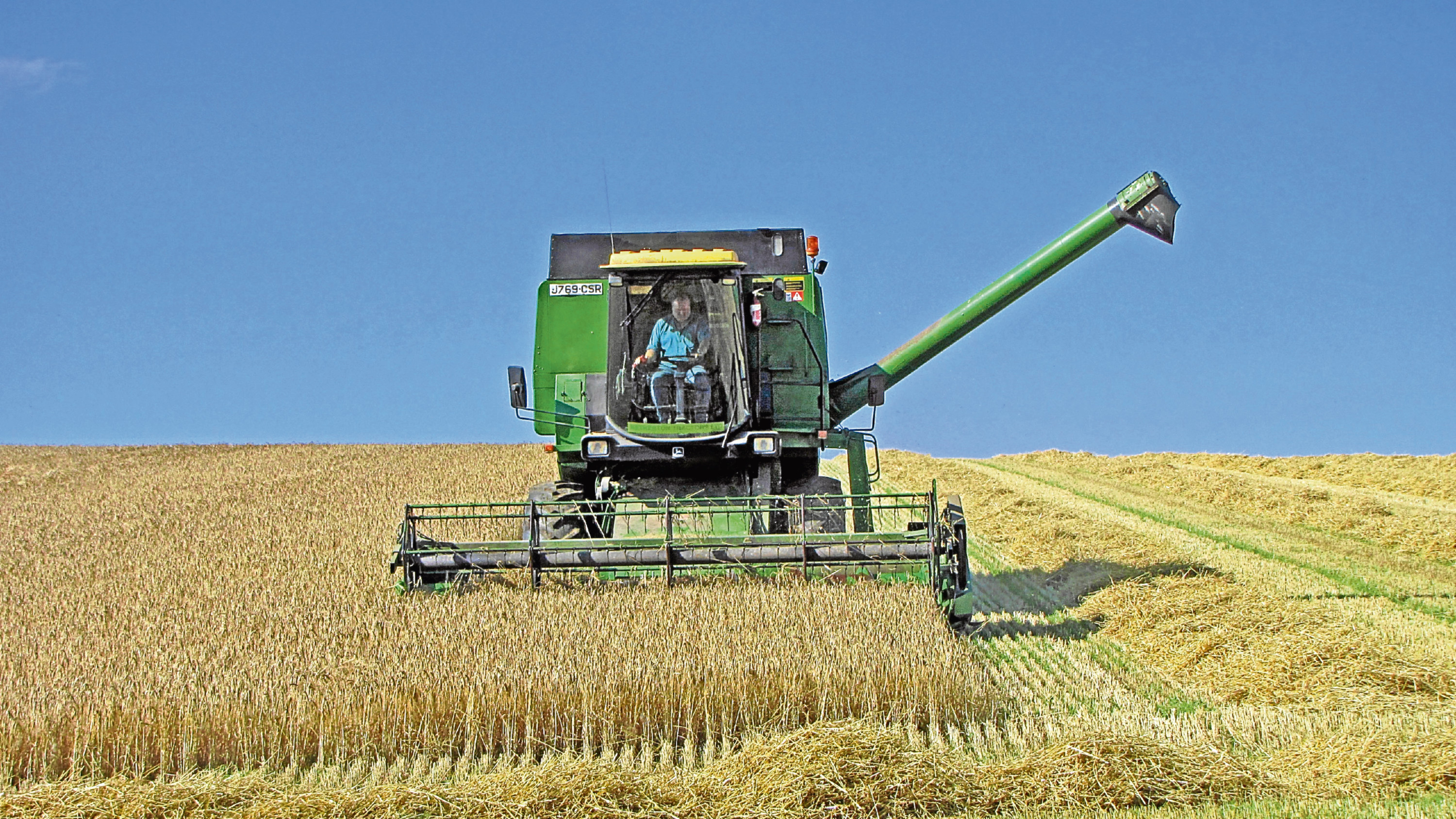 A combine harvester at work in a field near Kingoldrum, Angus.