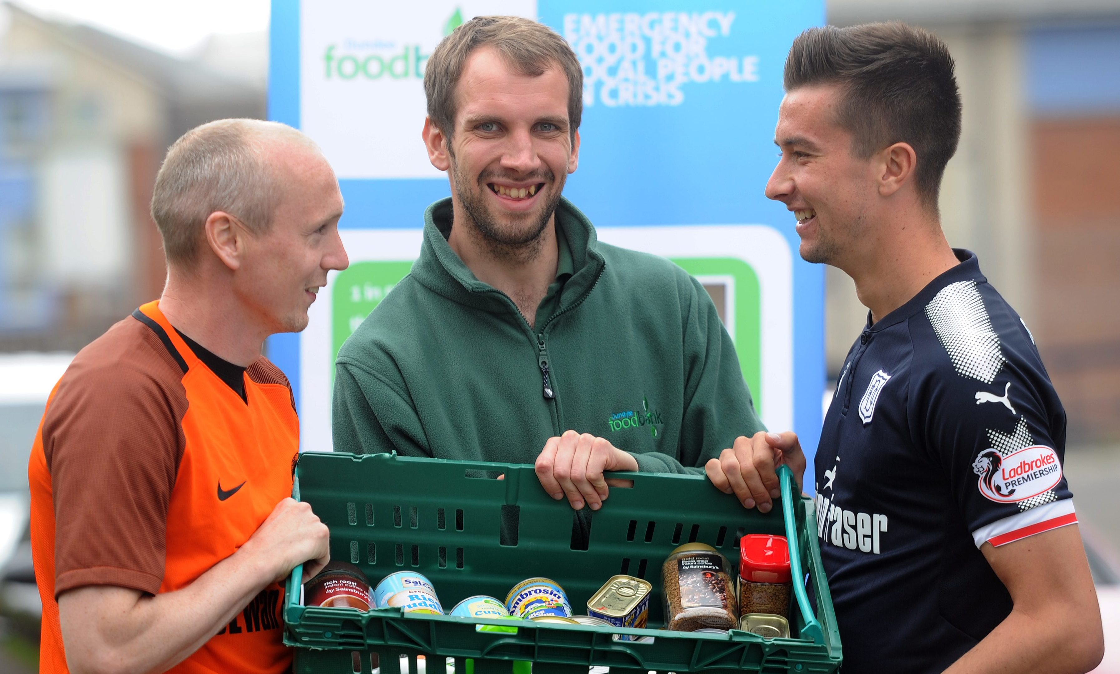 Willo Flood of United and Cammy Kerr of Dundee with Michael Calder, Foodbank stock co-ordinator.