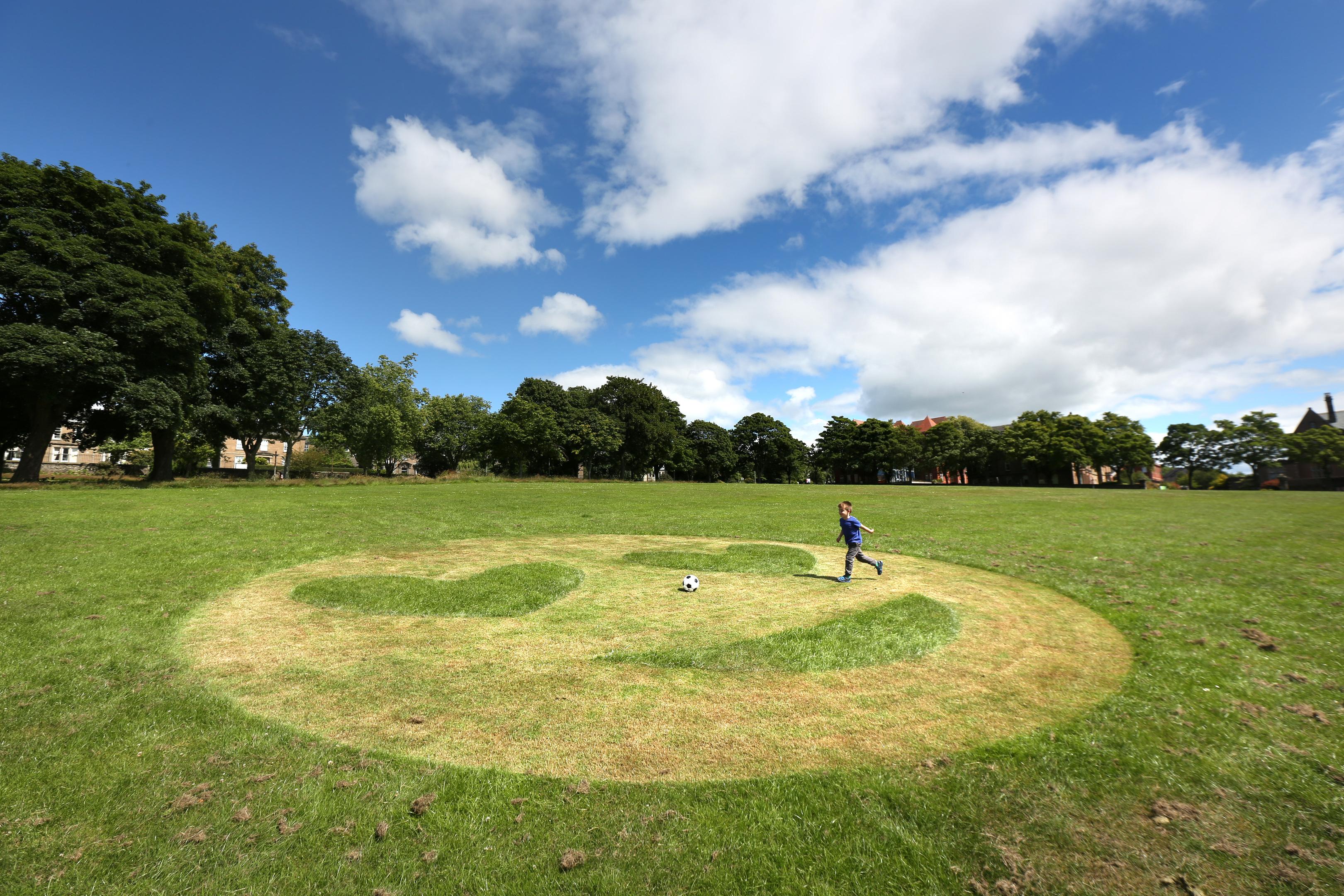 Murray Allan (4) playing football beside the emoji in Dudhope Park.