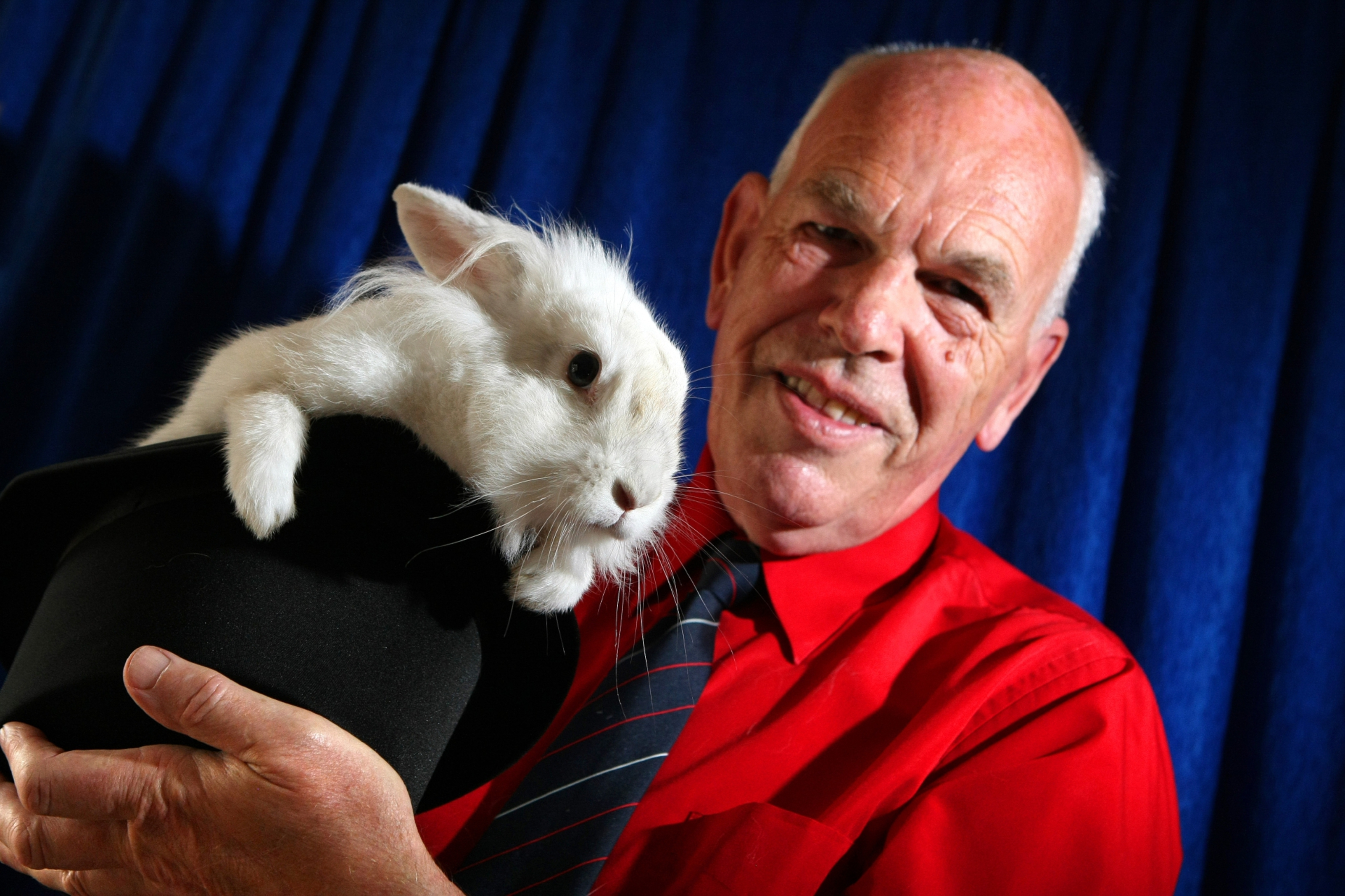 Perth magician Adrian Harris pulls Merlin the rabbit out of a hat.