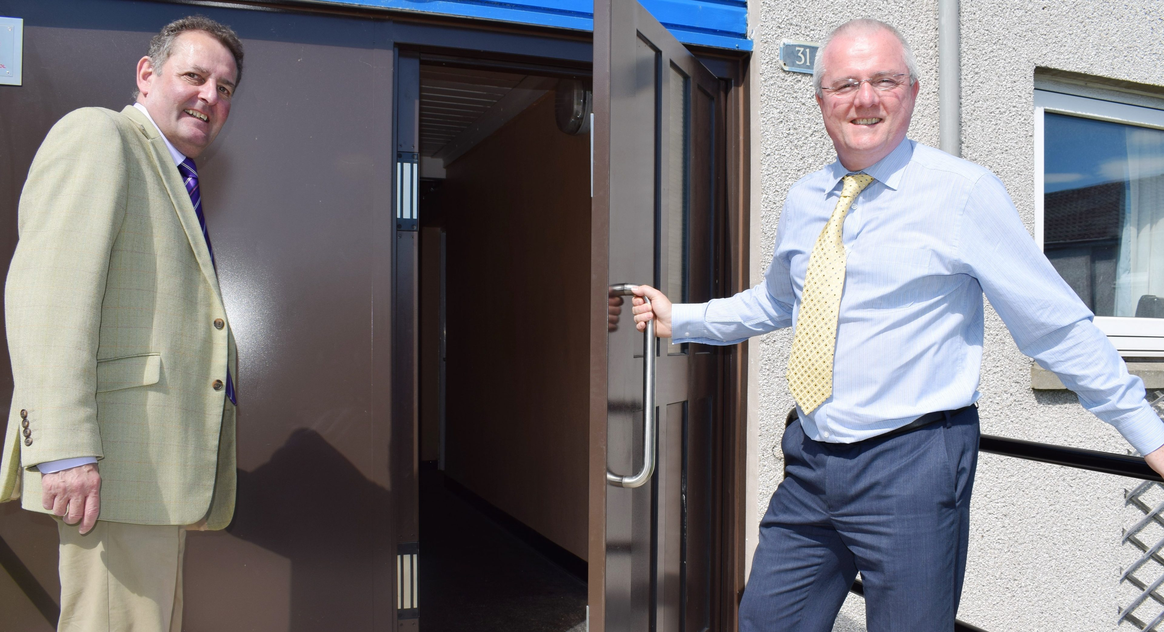 Councillors Harry Coates and Peter Barrett at a secure-door entry system in Perth.