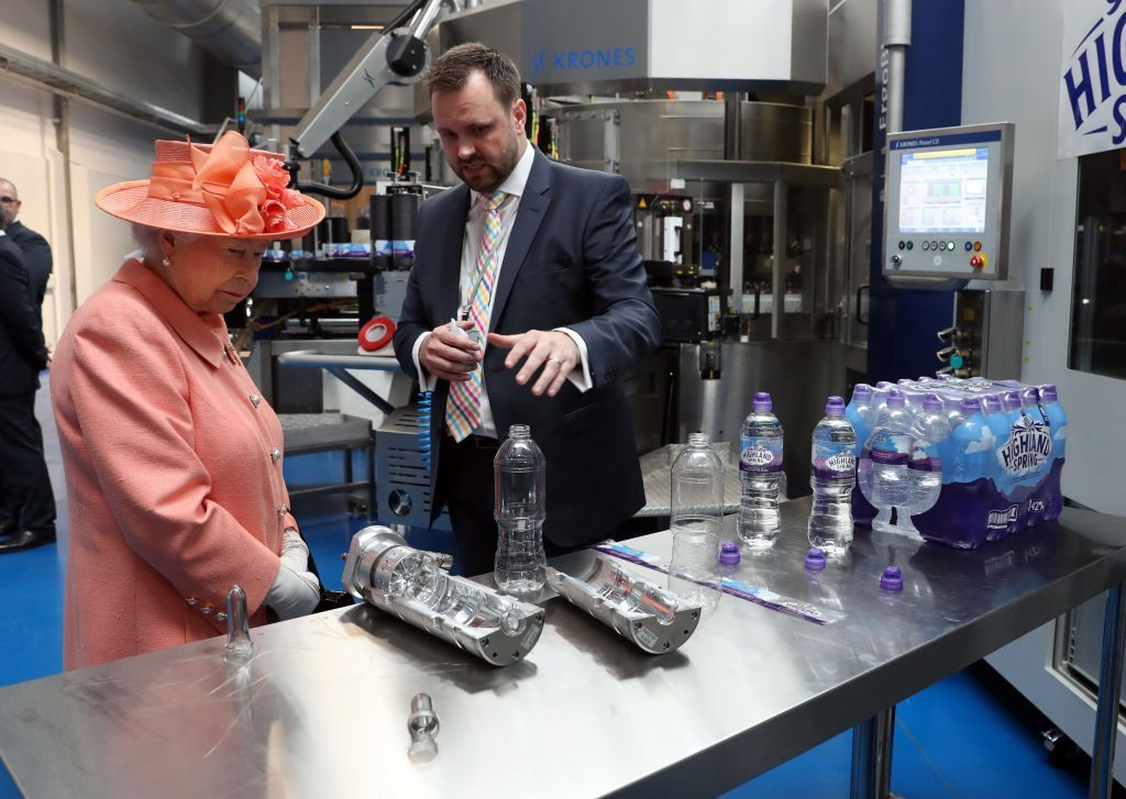 Queen Elizabeth II is shown the bottle making and filling process in the new bottling plant by Group Operations Director Bryan McCluskey.