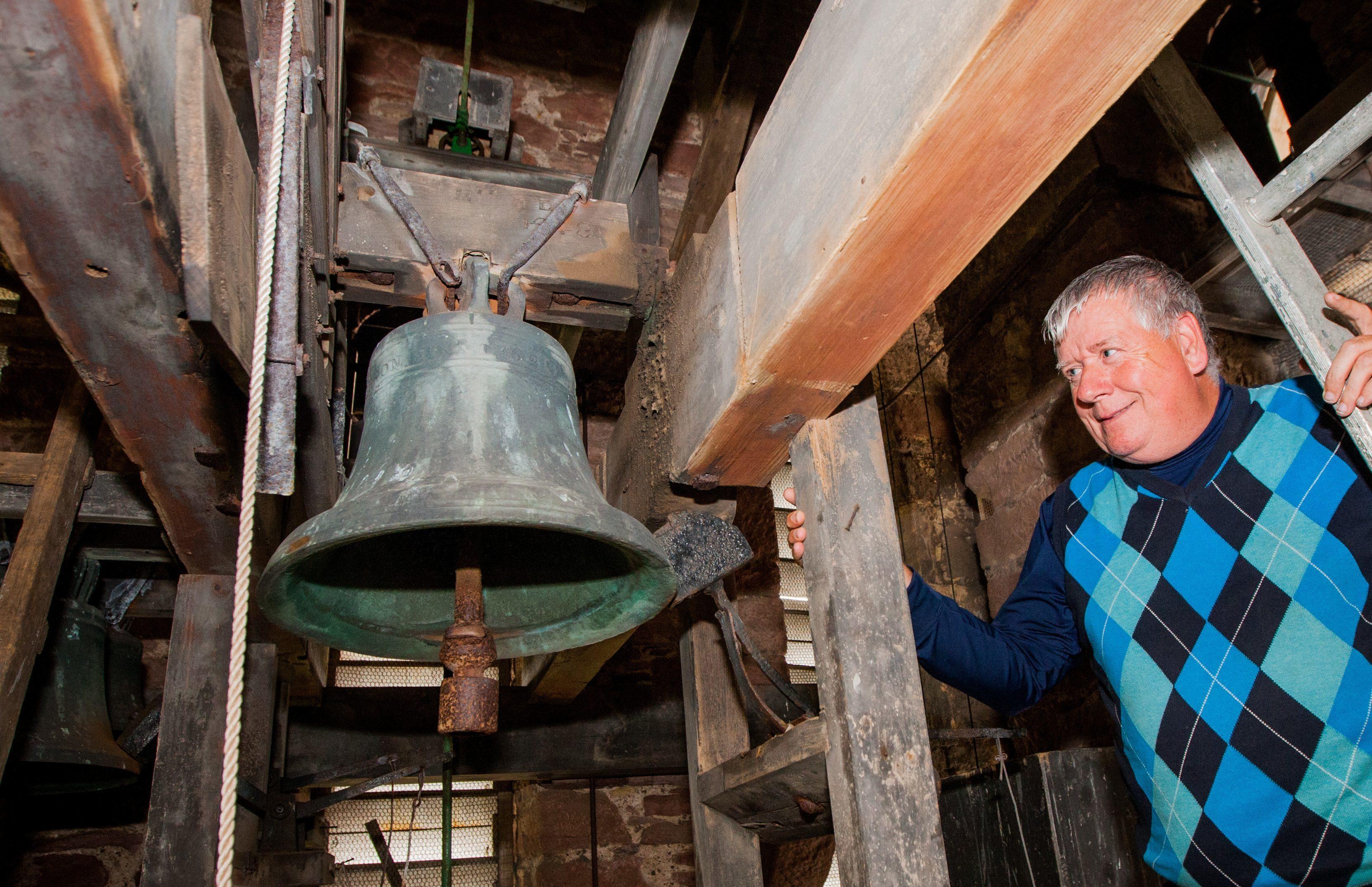 The Reverend John Macgregor alongside the bells at Errol Parish Church.