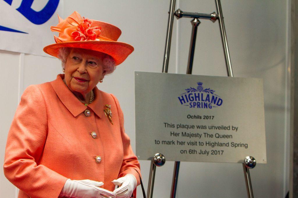 The Queen unveils a plaque.