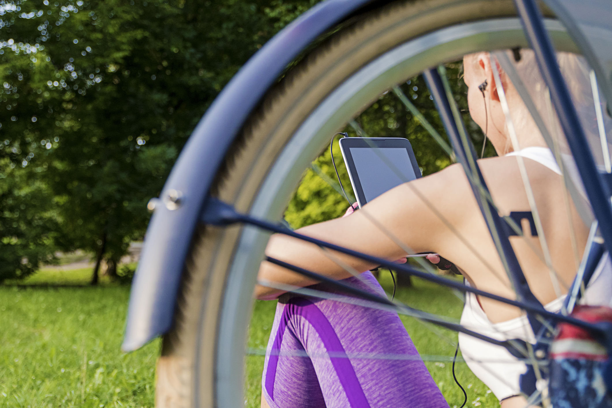 Fit young woman using digital tablet pc sitting next to her bike. Woman listening to the music from a tablet sitting  in a park with a bicycle in the background. pretty girl reading e-book on a sunny day.
