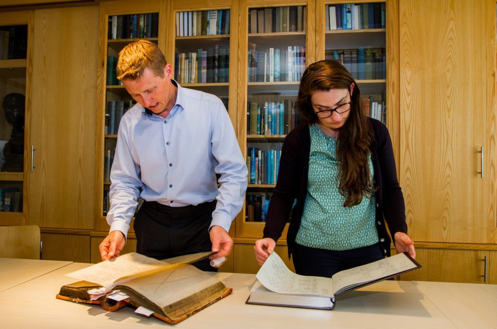 RSGS chief executive Mike Robinson  and RSGS communications officer Gemma McDonald with the restored visitor book and modern day visitor book.