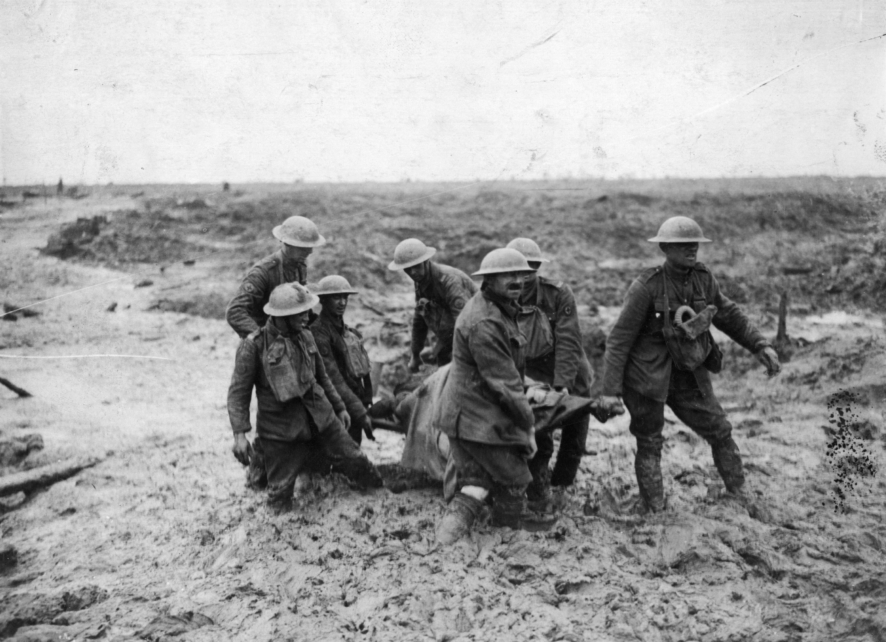 A stretcher party bear a wounded soldier through the mud at Passchendaele.