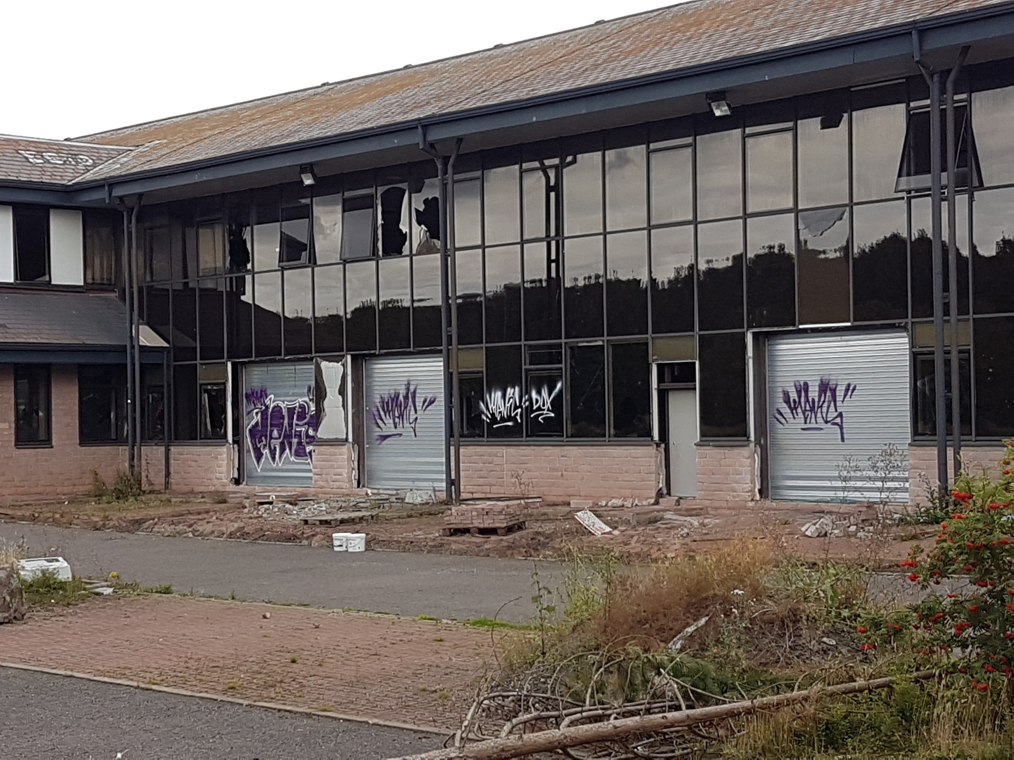 The building's windows have been smashed and its shutters are covered in graffiti.