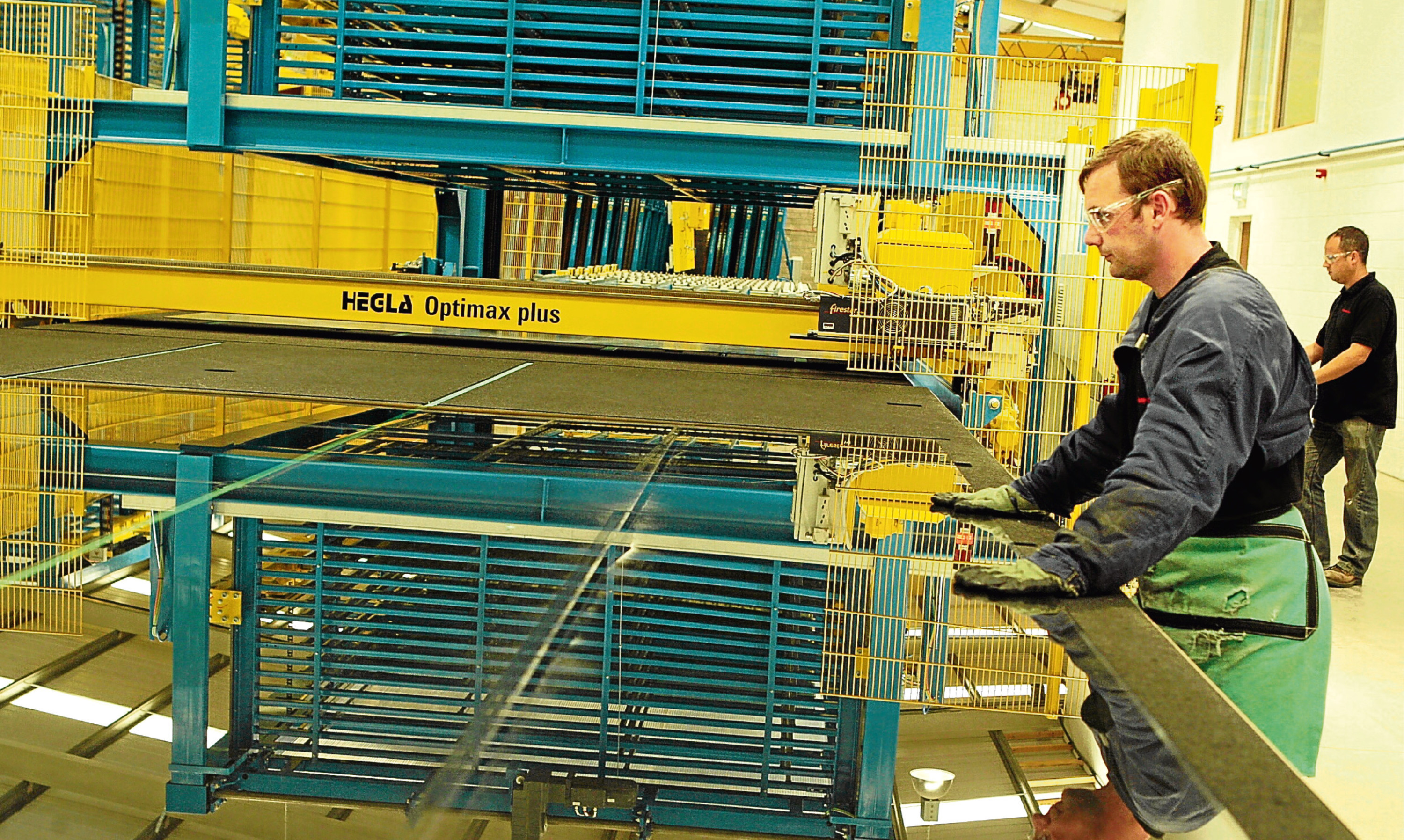 A Ravensby Glass employee examines a glass panel