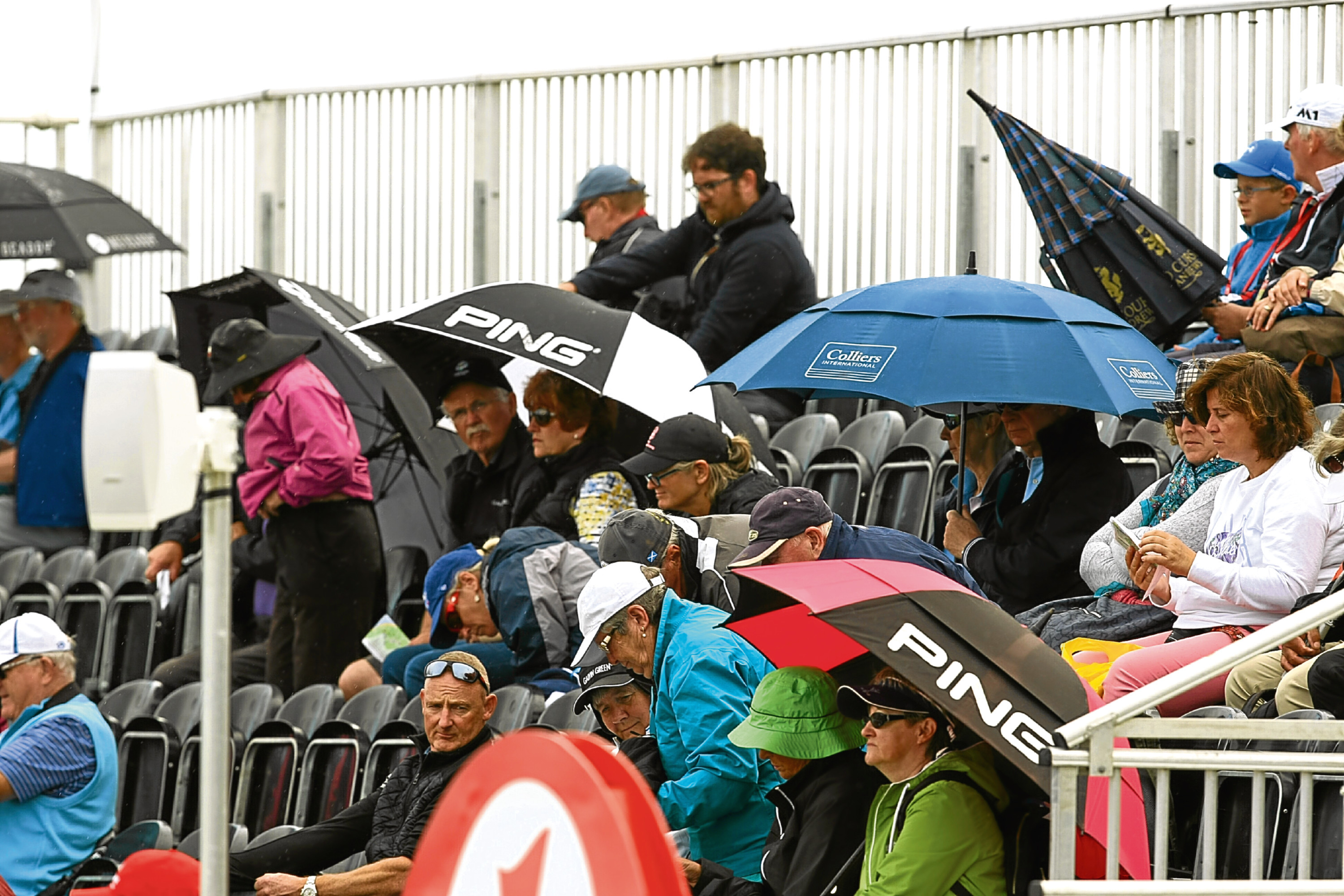 Golf fans take shelter from the rain again during the Women's British Open in high summer in Scotland.