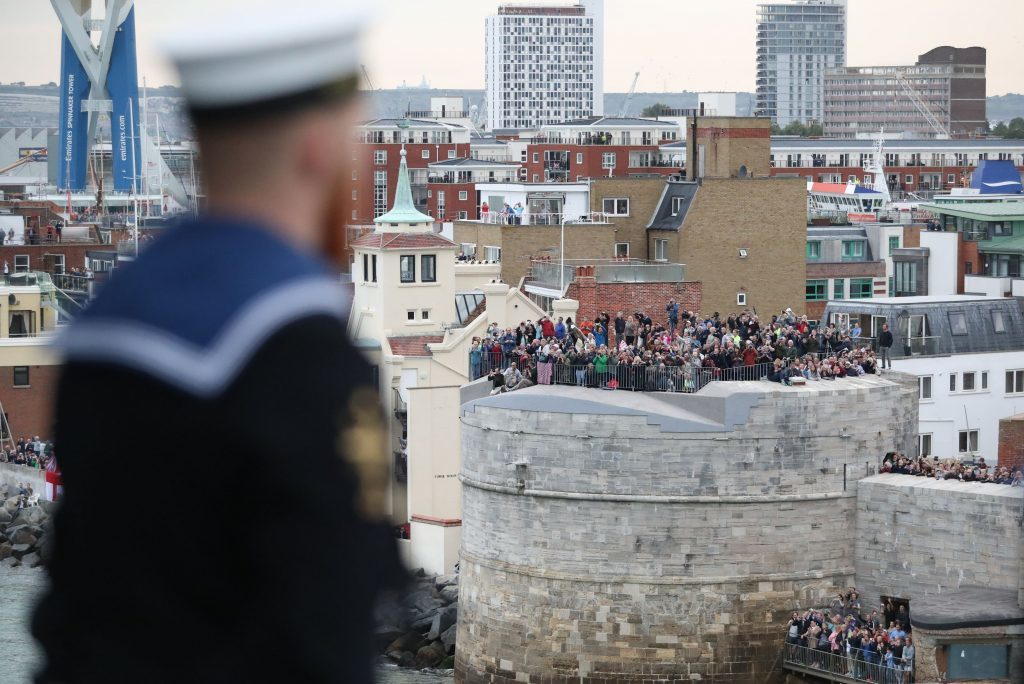 A sailor looks out at spectators on the Round Tower as HMS Queen Elizabeth