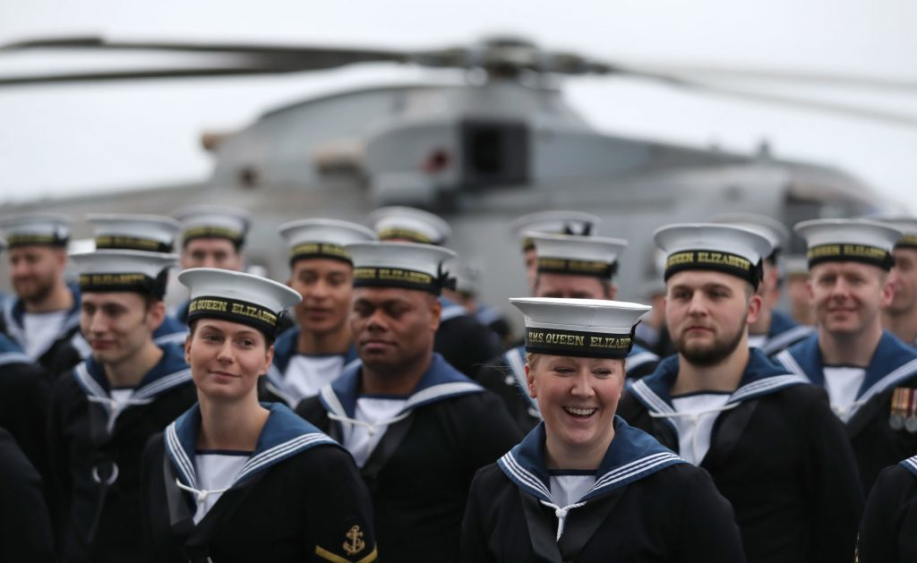 Ratings line the flight deck of HMS Queen Elizabeth, the UK's newest aircraft carrier, as she arrives in Portsmouth.