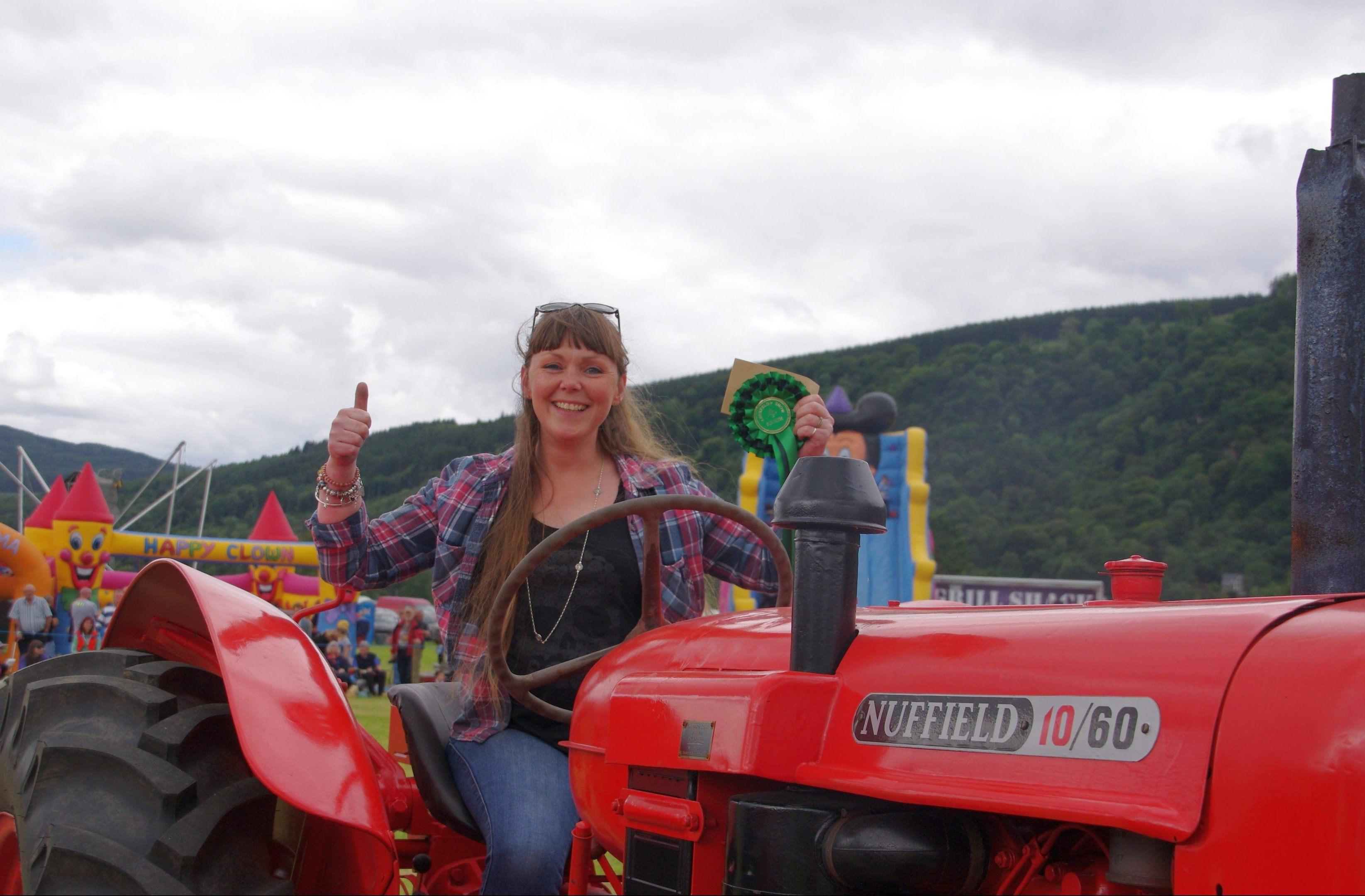 Claire Philip of Aberfeldy shows her delight in getting a fourth place rosette in the classic vintage tractor class.
