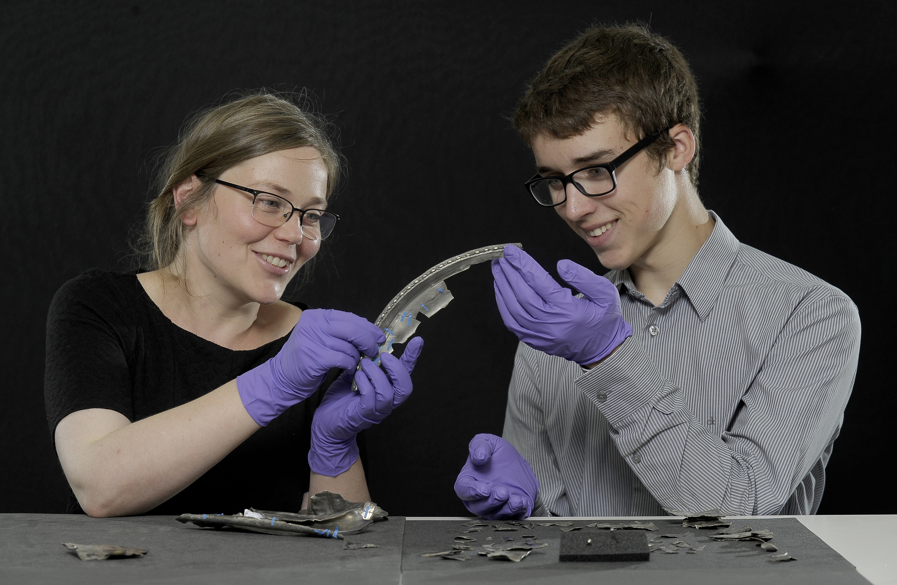 Metal detectorist David Hall, 16, examines the Dairsie Hoard, a hoard of Roman era silver he unearthed in Fife, with Glenmorangie Research Fellow Alice Blackwell of National Museums Scotland.