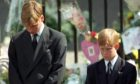 Prince William (left) and Prince Harry, the sons of Diana, Princess of Wales, bow their heads as their mother's coffin is taken out of Westminster Abbey following her funeral service.