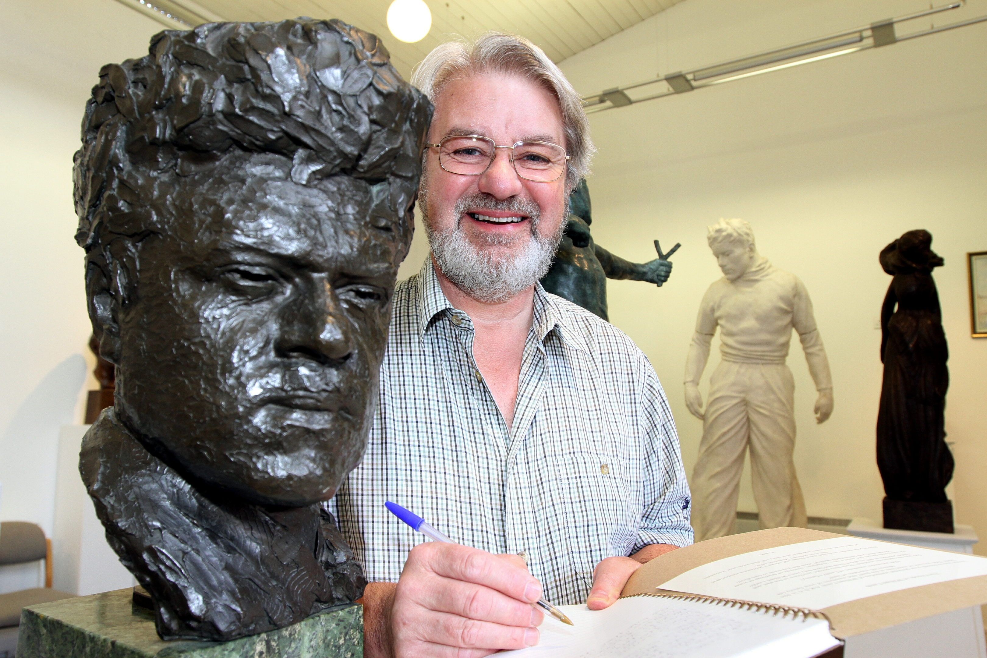 Friends chairman Norman Atkinson signs the memory book alongside a self-sculpture of the man himself.