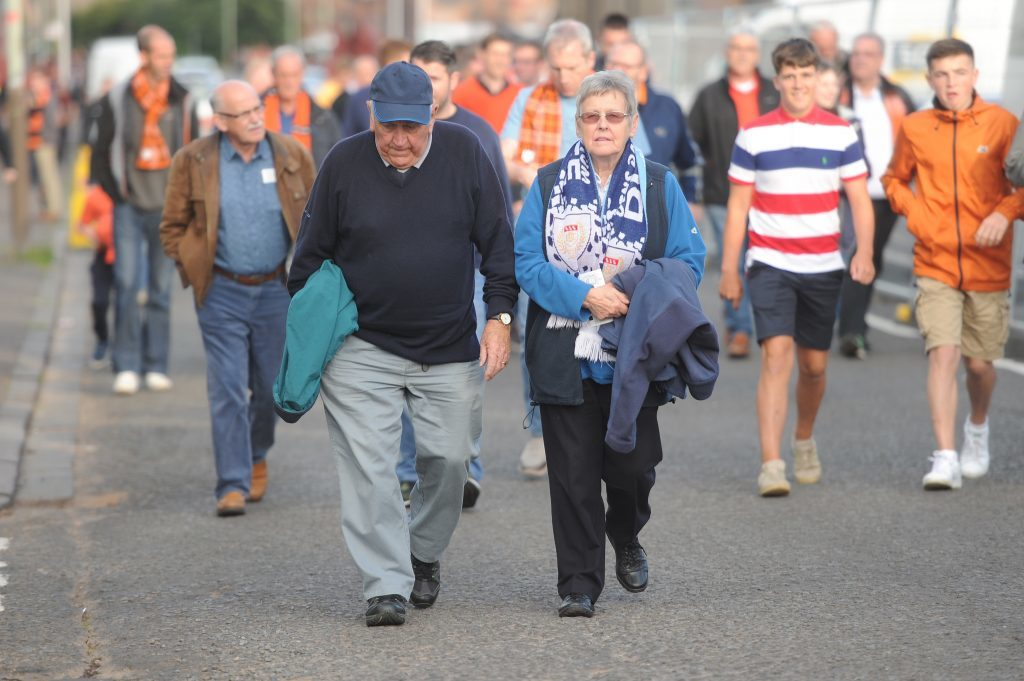 Fans of both clubs make their way to Dens Park before the start of the match.