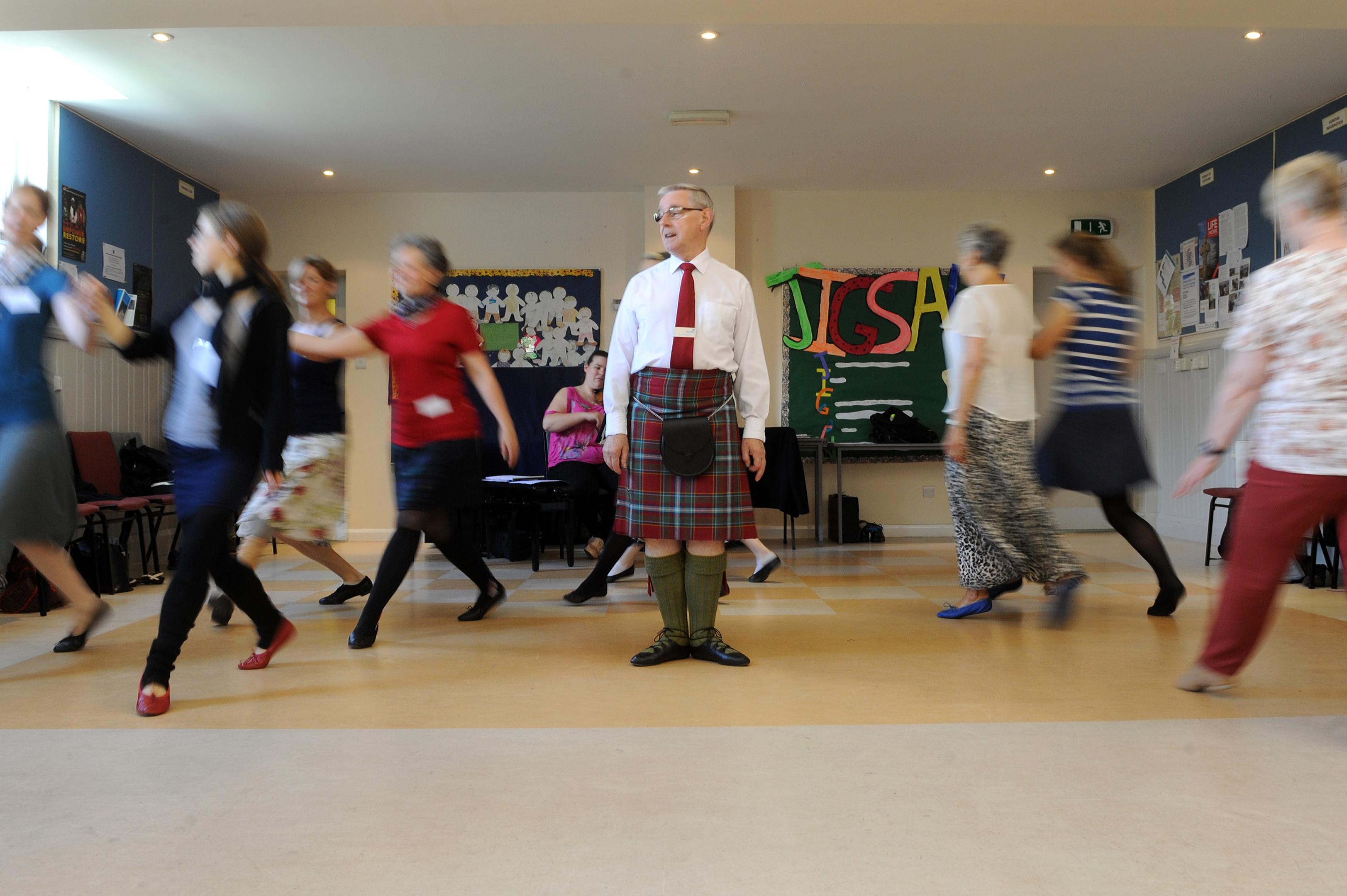 s; John Wilkinson instructing a dance class with violinist, Shona MacFadyen,