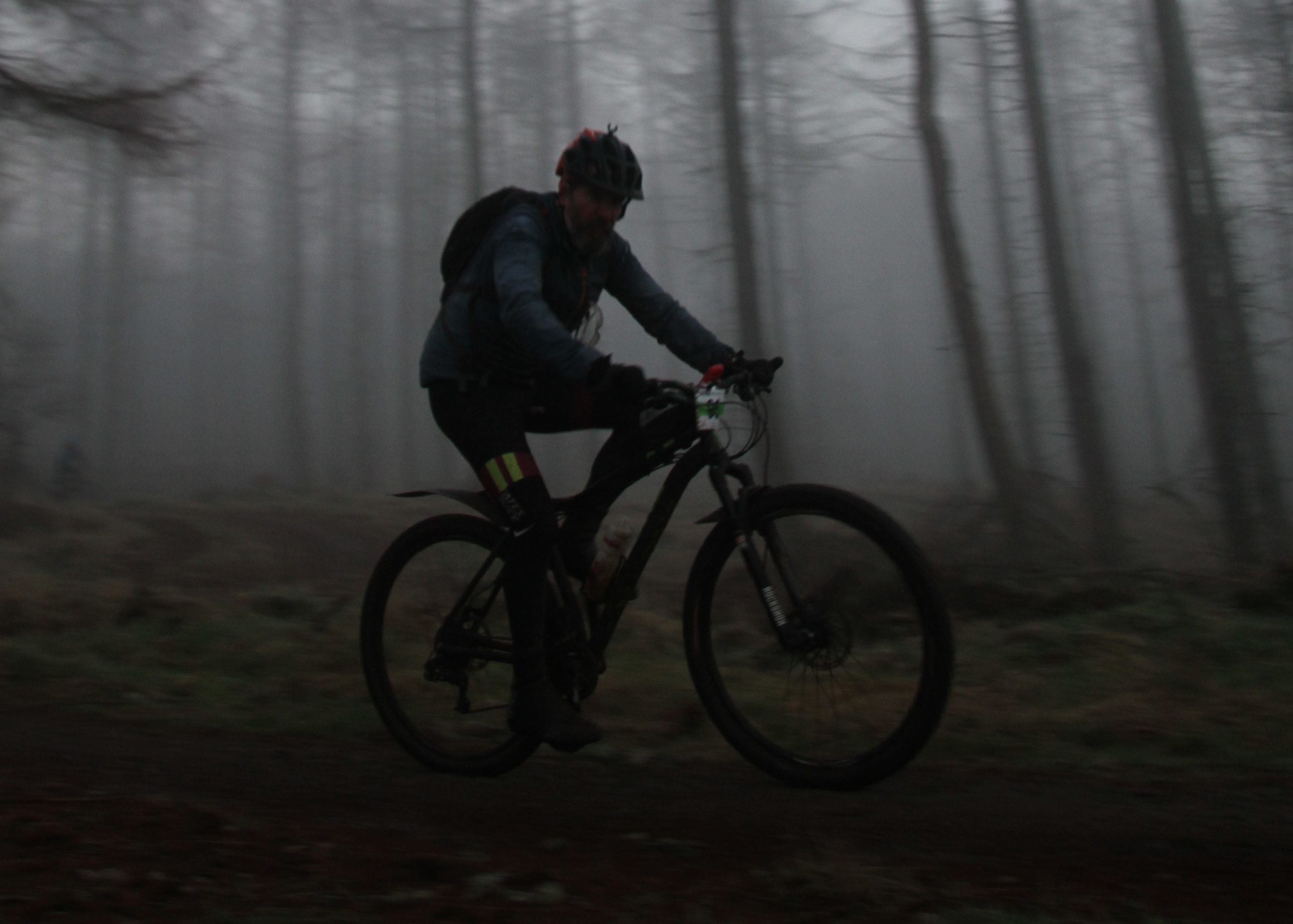Night starts to fall at the Strathpuffer. Scot riding through the lower forest .