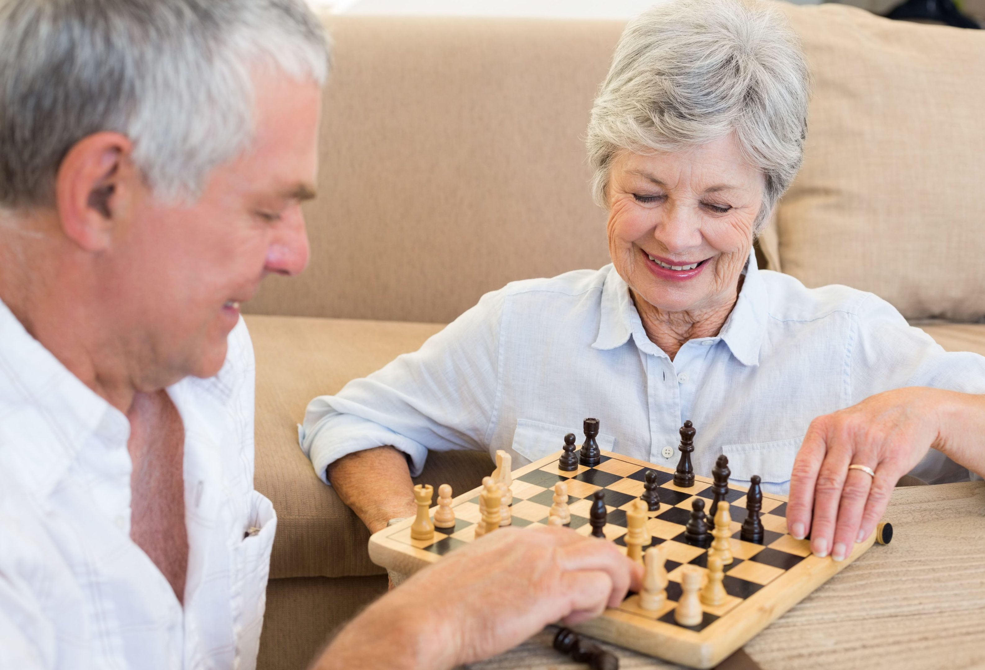 An older couple playing chess together. But what is the secret to a happy retirement?