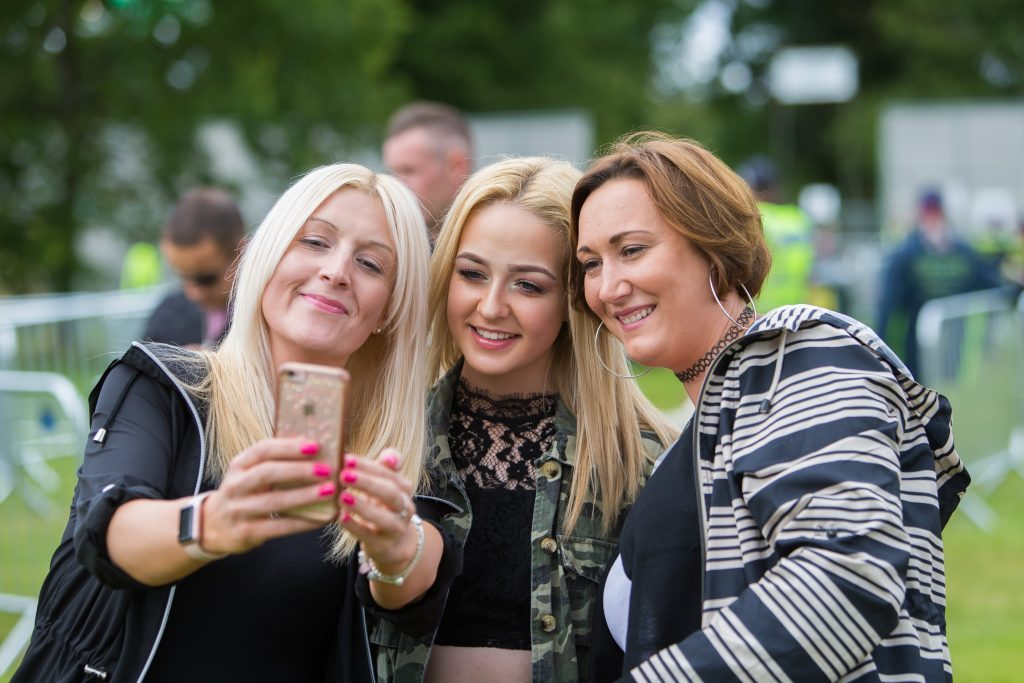 A family prepare for a selfie at Carnival 56