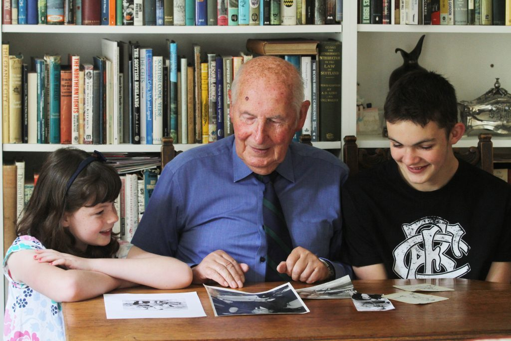 Retired journalist Ian Nimmo with grandchildren Zoë and Duncan looking at images of their Father/Great Grandfather at Dunkirk.