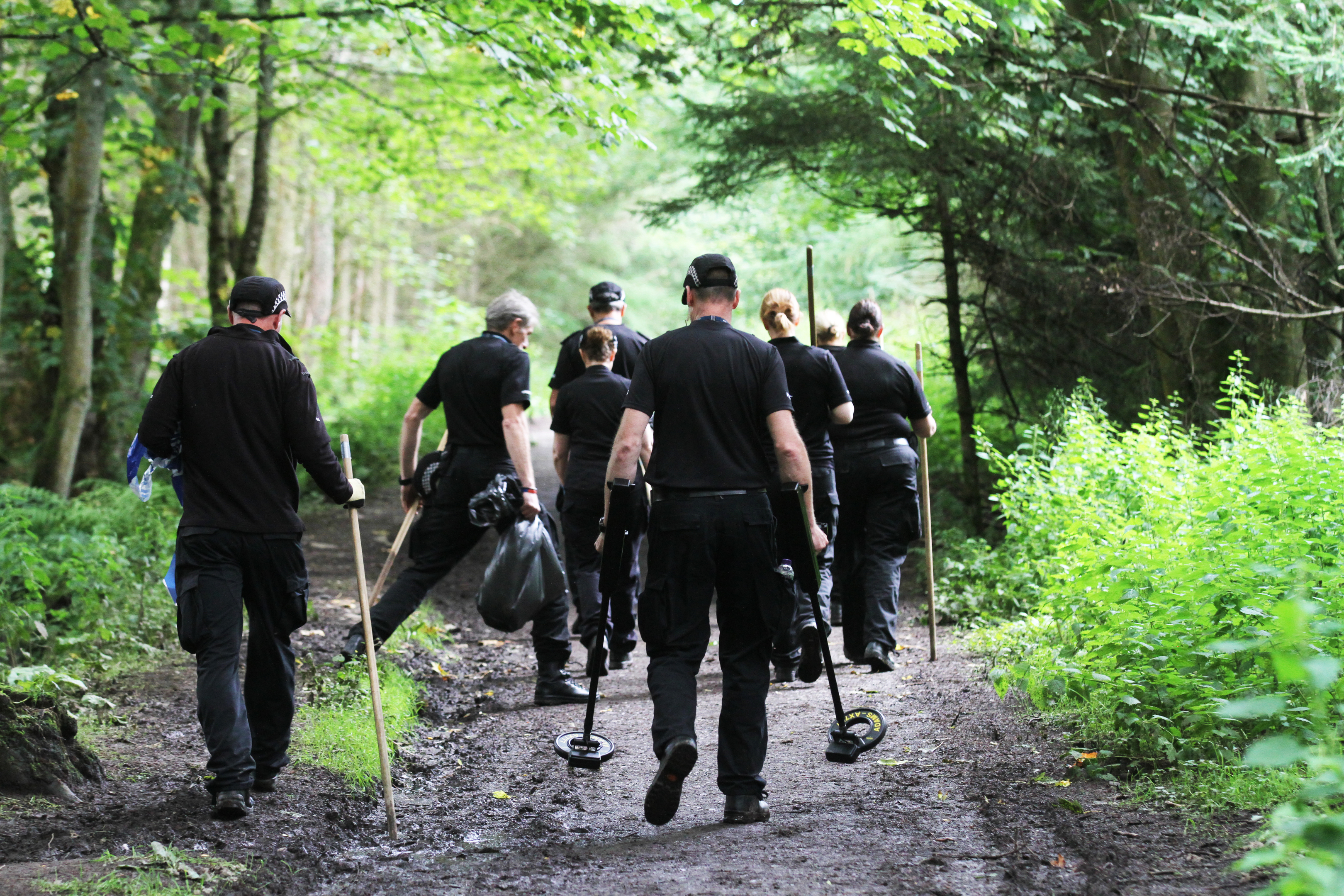 Police teams searching Templeton Woods for evidence.