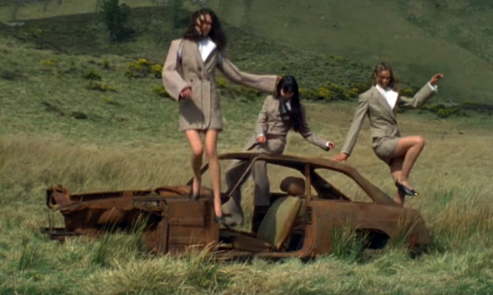 Models posed on a rusty car for the McCartney shoot