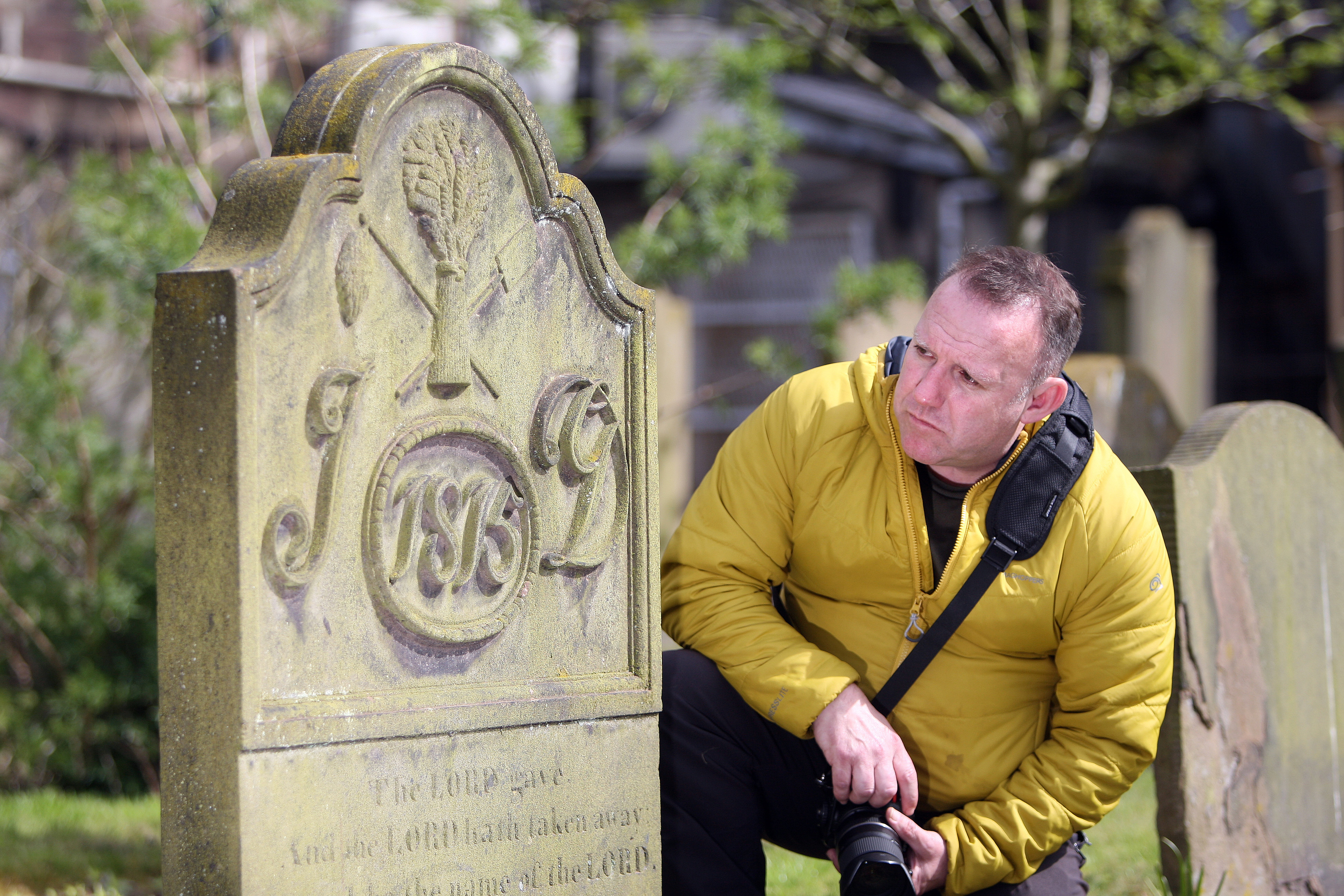 Simon Goulding, Chair of the Howff Conservation Group in front of a grave detailed with a Bakers trade symbol.