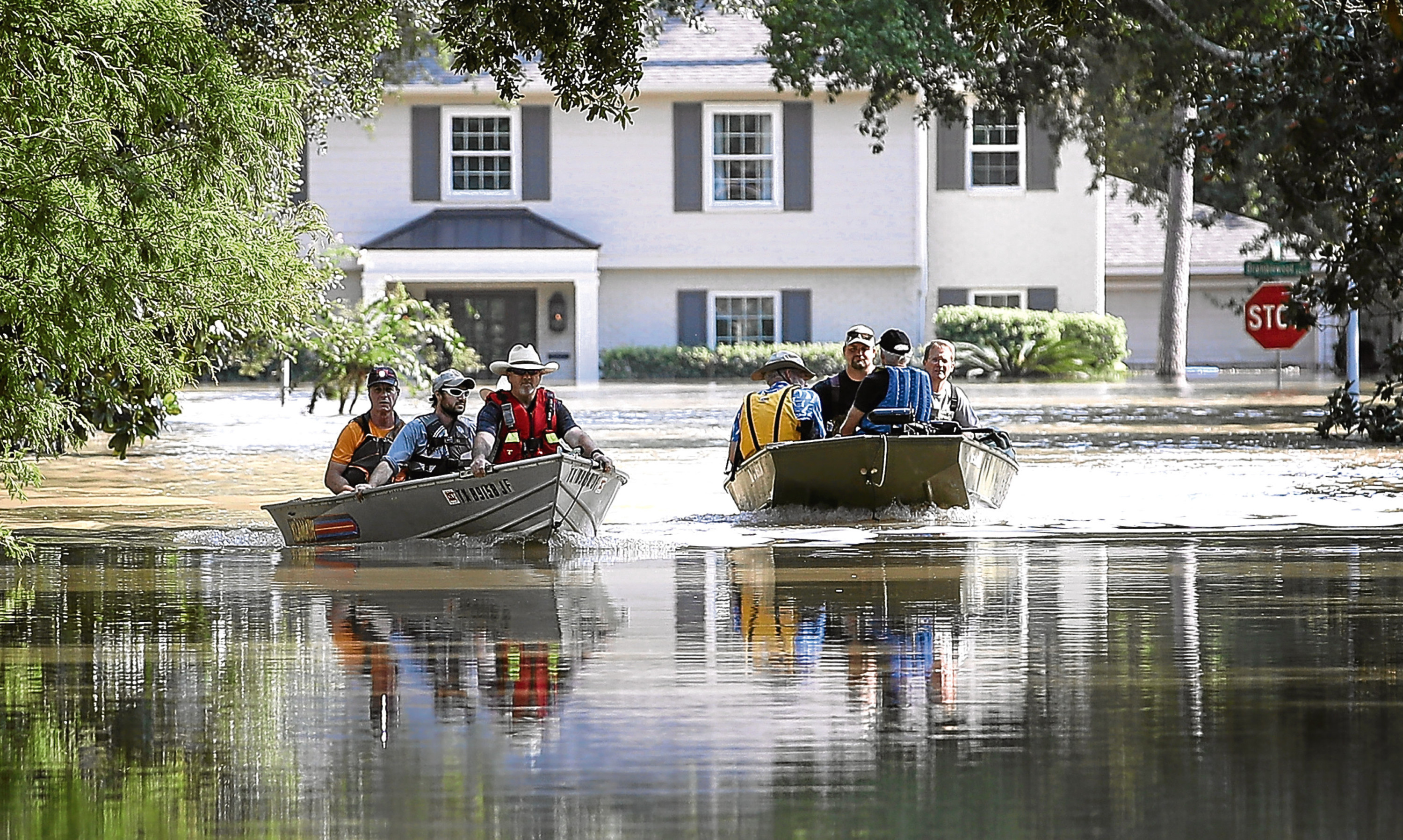 Residents near the Barker Reservoir, Houston, Texas, return to their flooded homes to collect belongings.