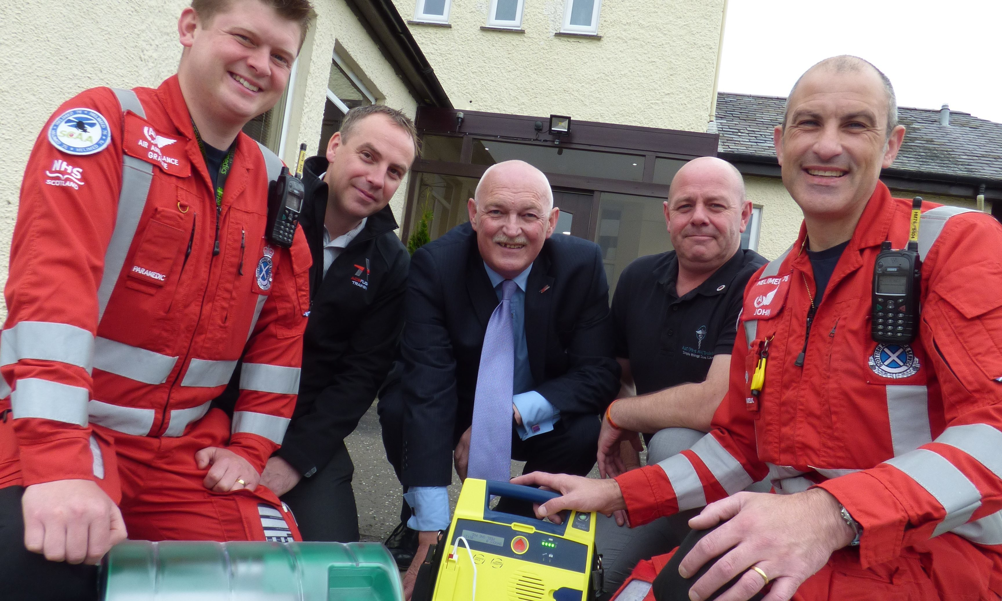 Steve Jeffs (centre) of Cardiac Science hands over the defibrillator to SCAA paramedic Graeme Hay (left) and lead paramedic John Pritchard (right) along with Graeme Frater of Perth Airport operators ACS Aviation (second from left) and Alan Moffat of A & E (First Aid) Training (second from right).